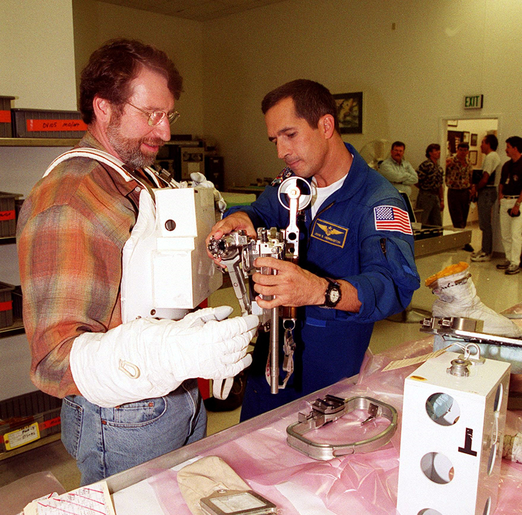 "KENNEDY SPACE CENTER, FLA. -- Astronaut John Herrington (right) helps Norm Abram try on a tool carrier used in space. Abram is the master carpenter on television's ""This Old House."" He is at KSC to film an episode of the series"