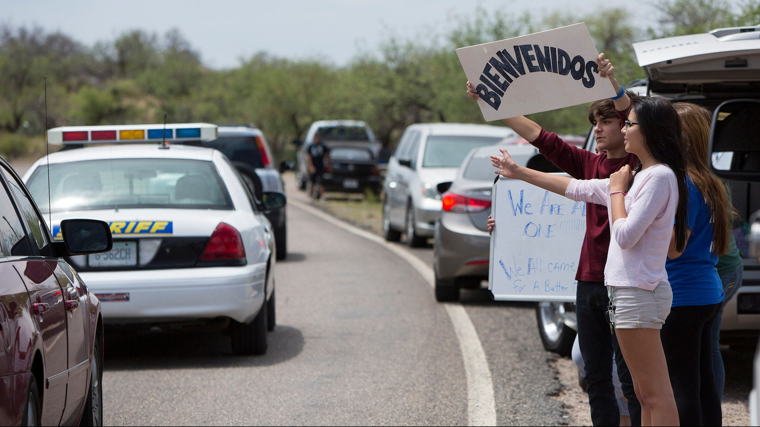 """Marcus Martinez of Oracle, Arizona, holds up a sign in Spanish that reads """"Welcome"""" as he and other members of his family watch as vehicles leave a demonstration against the arrival of undocumented immigrants in Oracle, Arizona July 15, 2014. In a scene reminiscent of similar protests in California, about 65 demonstrators gathered at a fork in the road near the small town of Oracle to complain that the federal government's response to a surge of new arrivals from Central America was putting their communities at risk."""