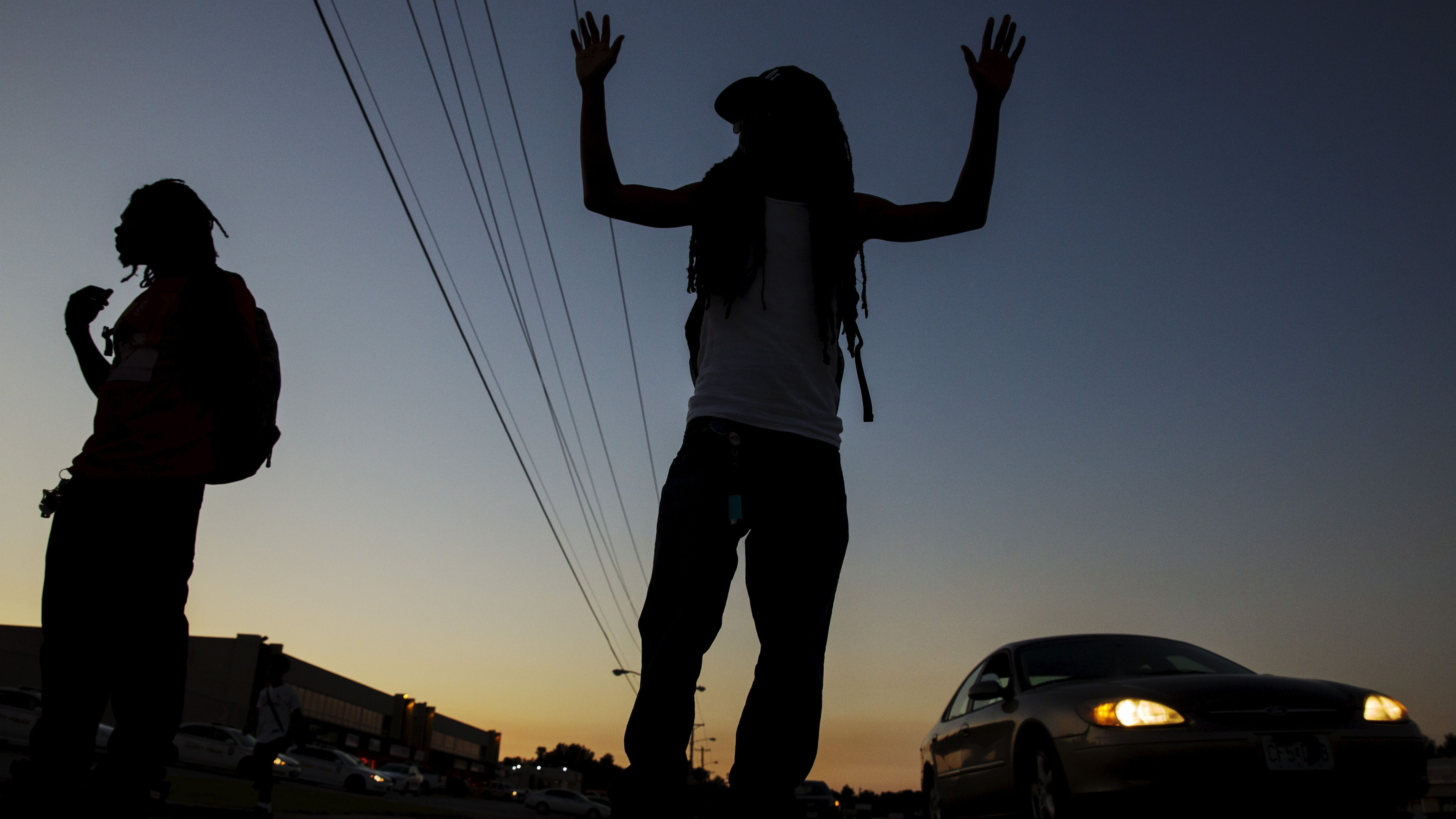 A man gestures on the side of West Florissant Ave. as a much smaller group of demonstrators prepare to protest for another night in Ferguson, Missouri
