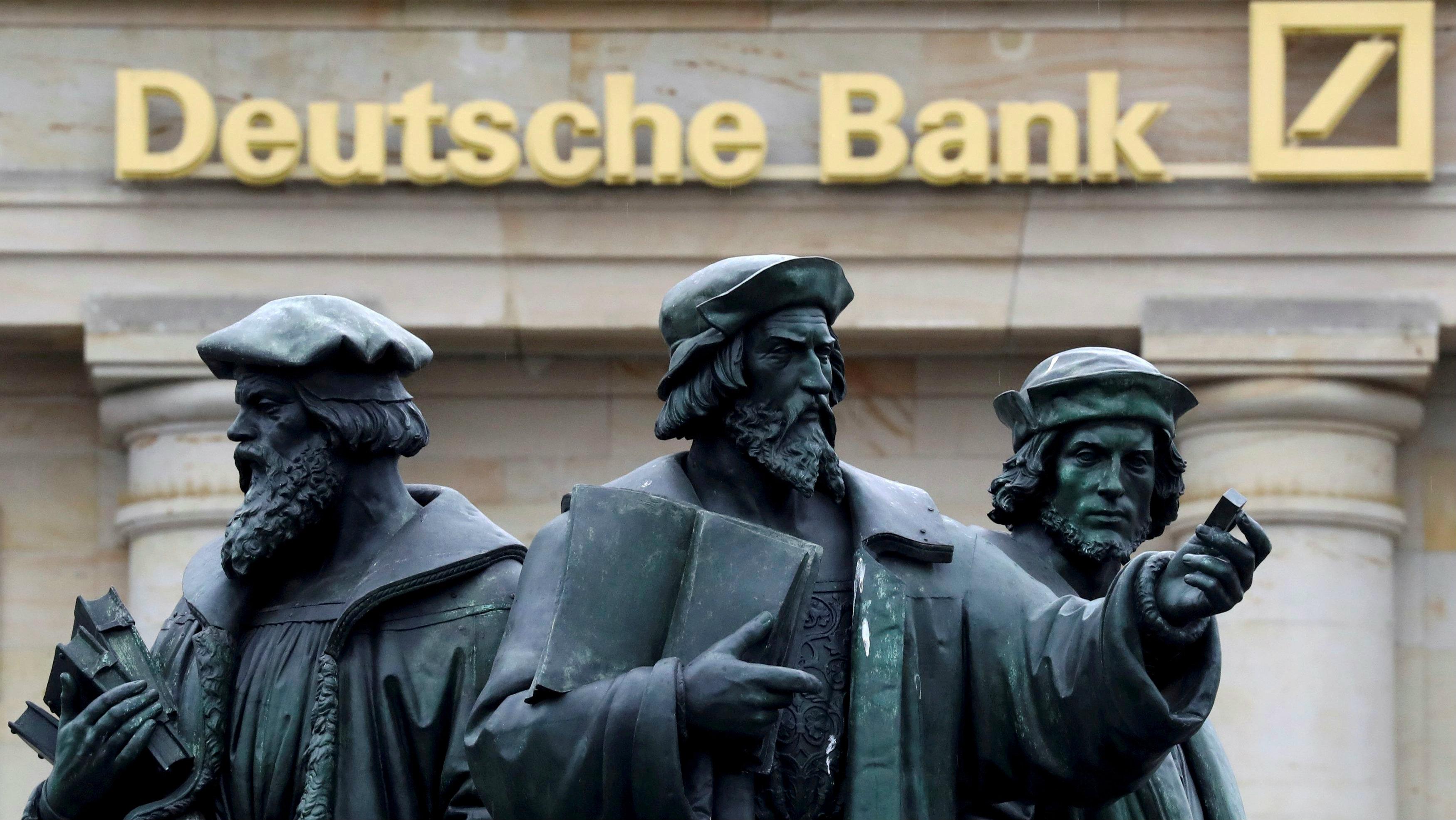 Statue next to the logo of Germany's Deutsche Bank in Frankfurt