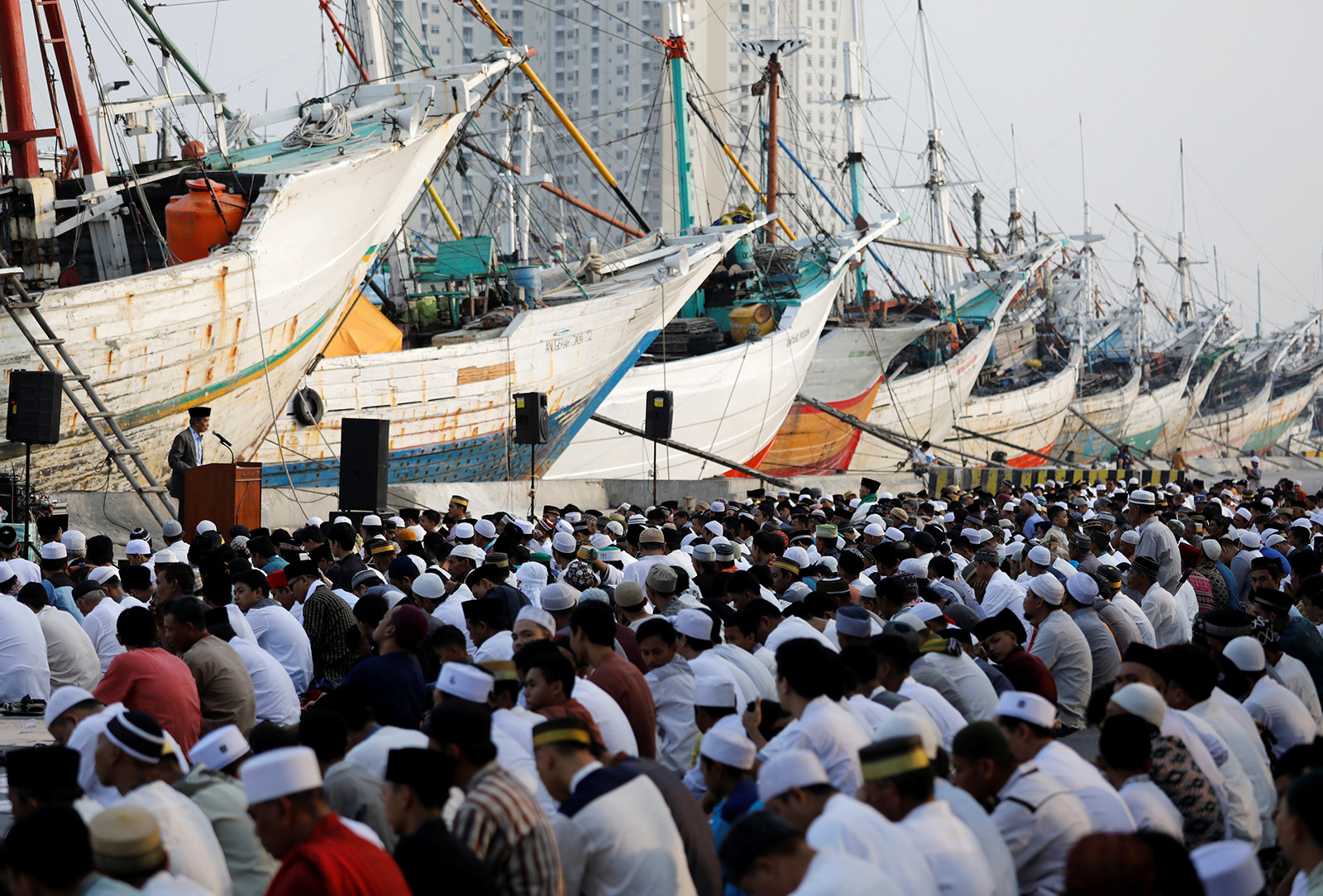 Muslims attend prayers to celebrate Eid al-Fitr, marking the end of the holy fasting month of Ramadan, at Sunda Kelapa port in Jakarta