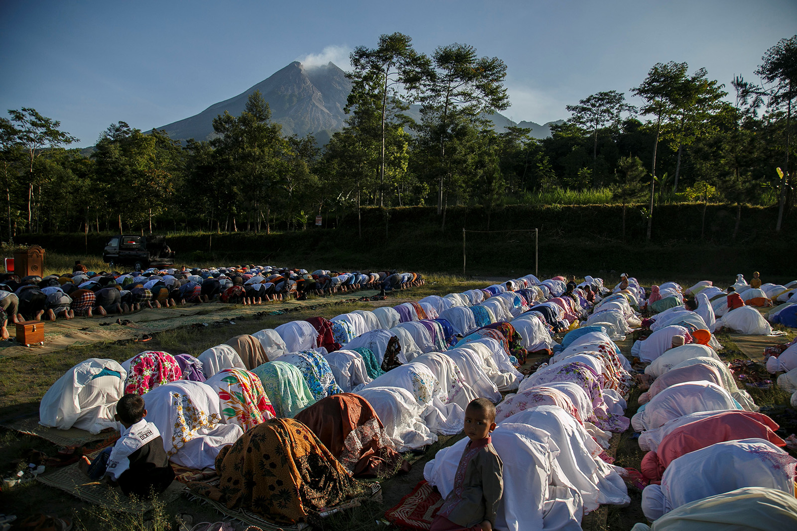 Muslims perform prayers to celebrate Eid al-Fitr, marking the end of the holy fasting month of Ramadan, near Mount Merapi volcano in Sleman Regency, Yogyakarta