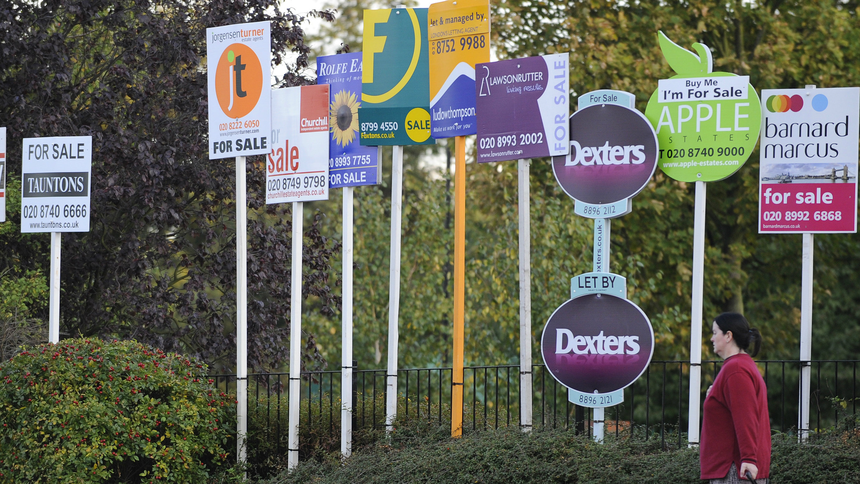 A woman passes property signs in west London