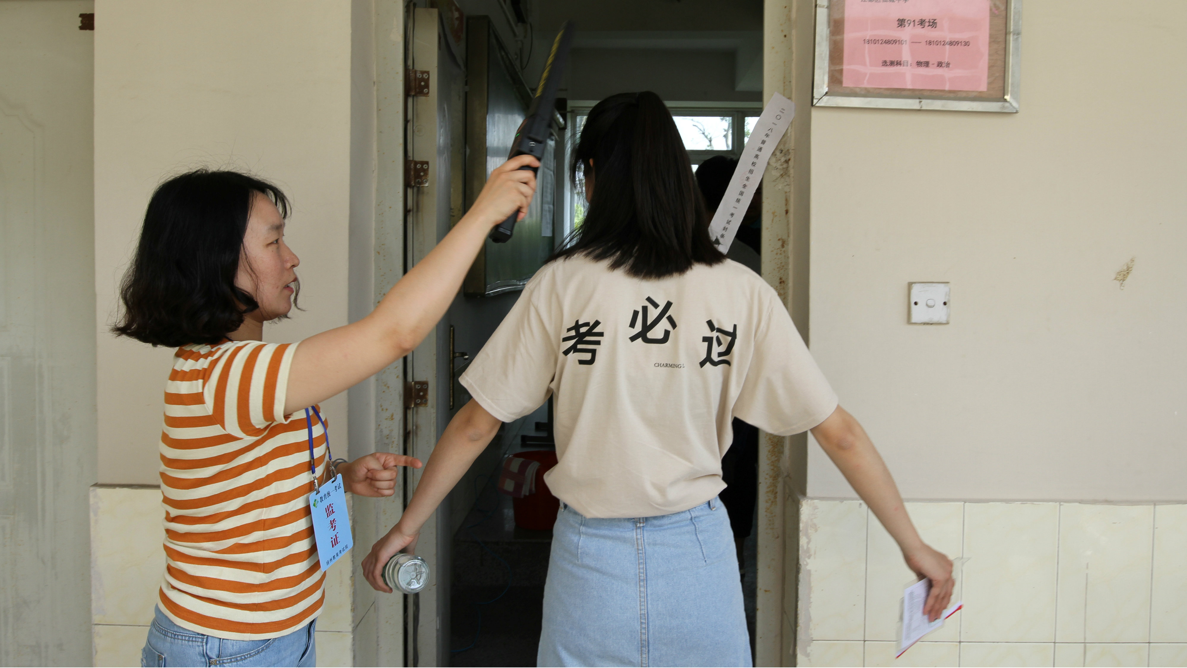 "A student is checked with a metal detector before she enters a classroom for the annual national college entrance examination, or ""gaokao"", in Yangzhou, Jiangsu province, China June 7, 2018."