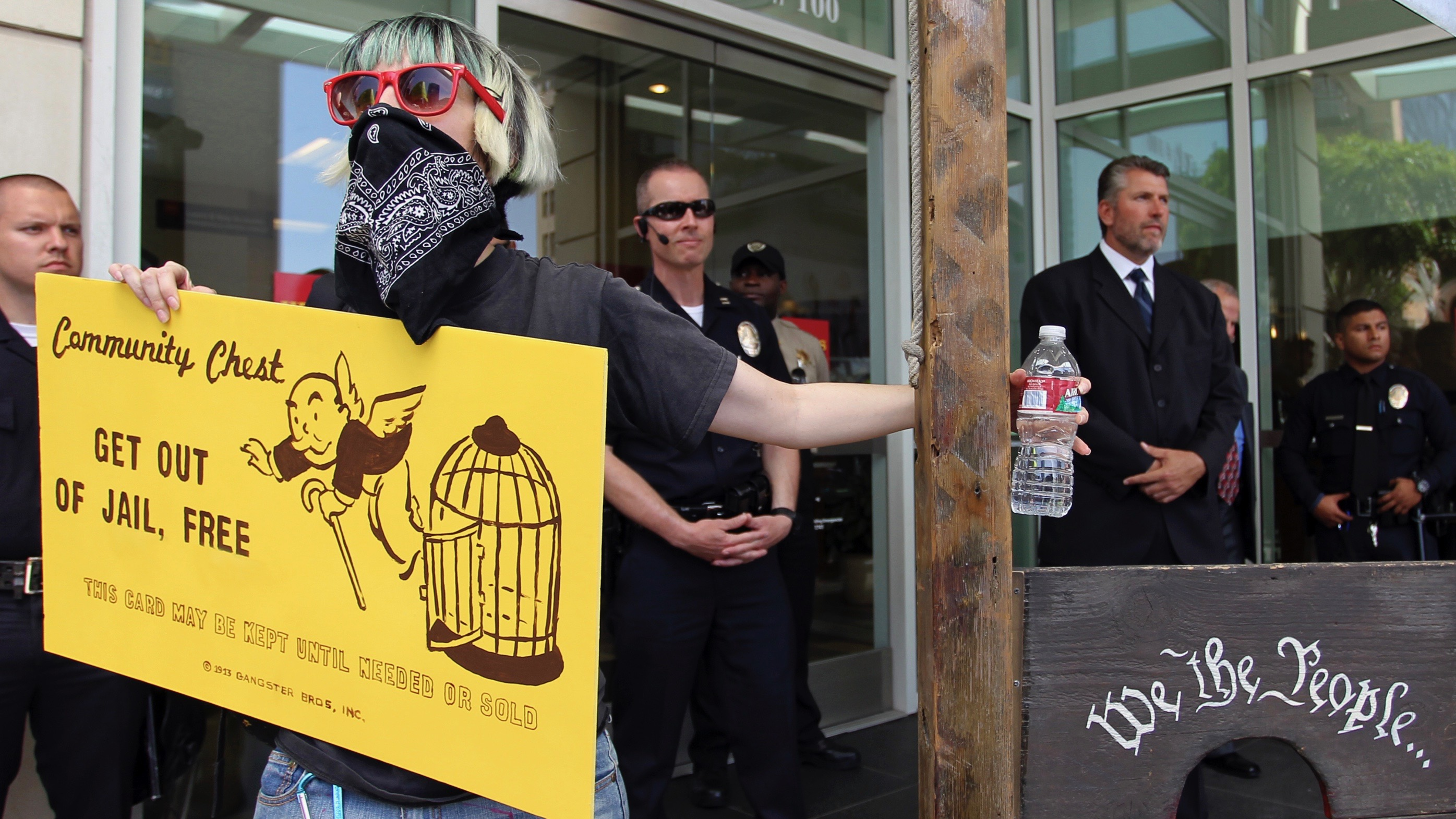 """An Occupy protestor holds a giant """"get out of jail, free"""" card."""