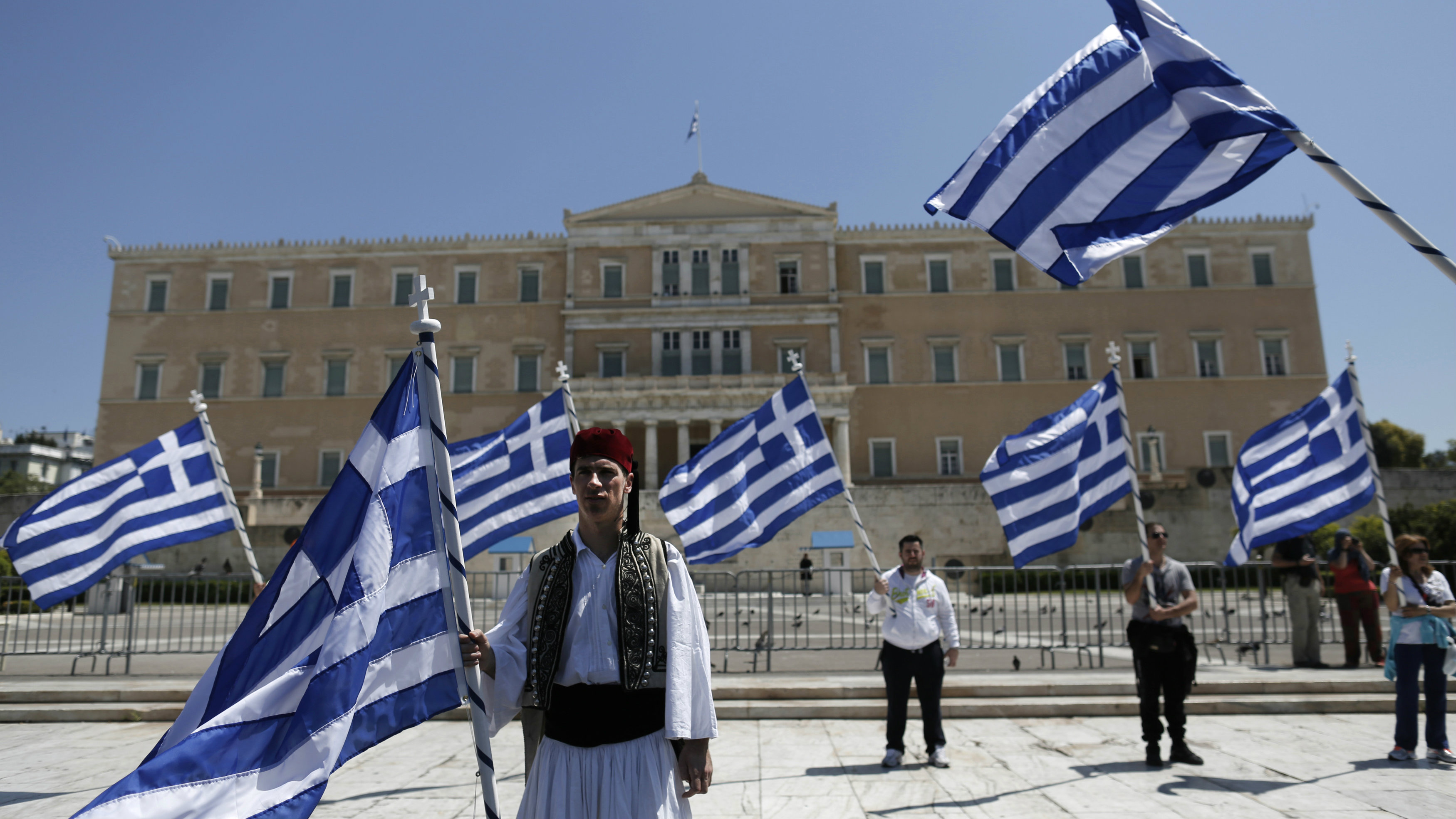 A municipal worker dressed in a traditional costume protests outside parliament in Athens