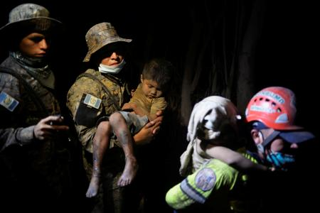 A soldier takes a rescued child covered with ash to a hospital after Fuego volcano erupted violently in El Rodeo, Guatemala June 3, 2018.