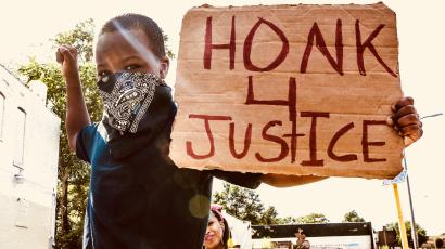 """Kid with sign saying """"honk4justice."""""""