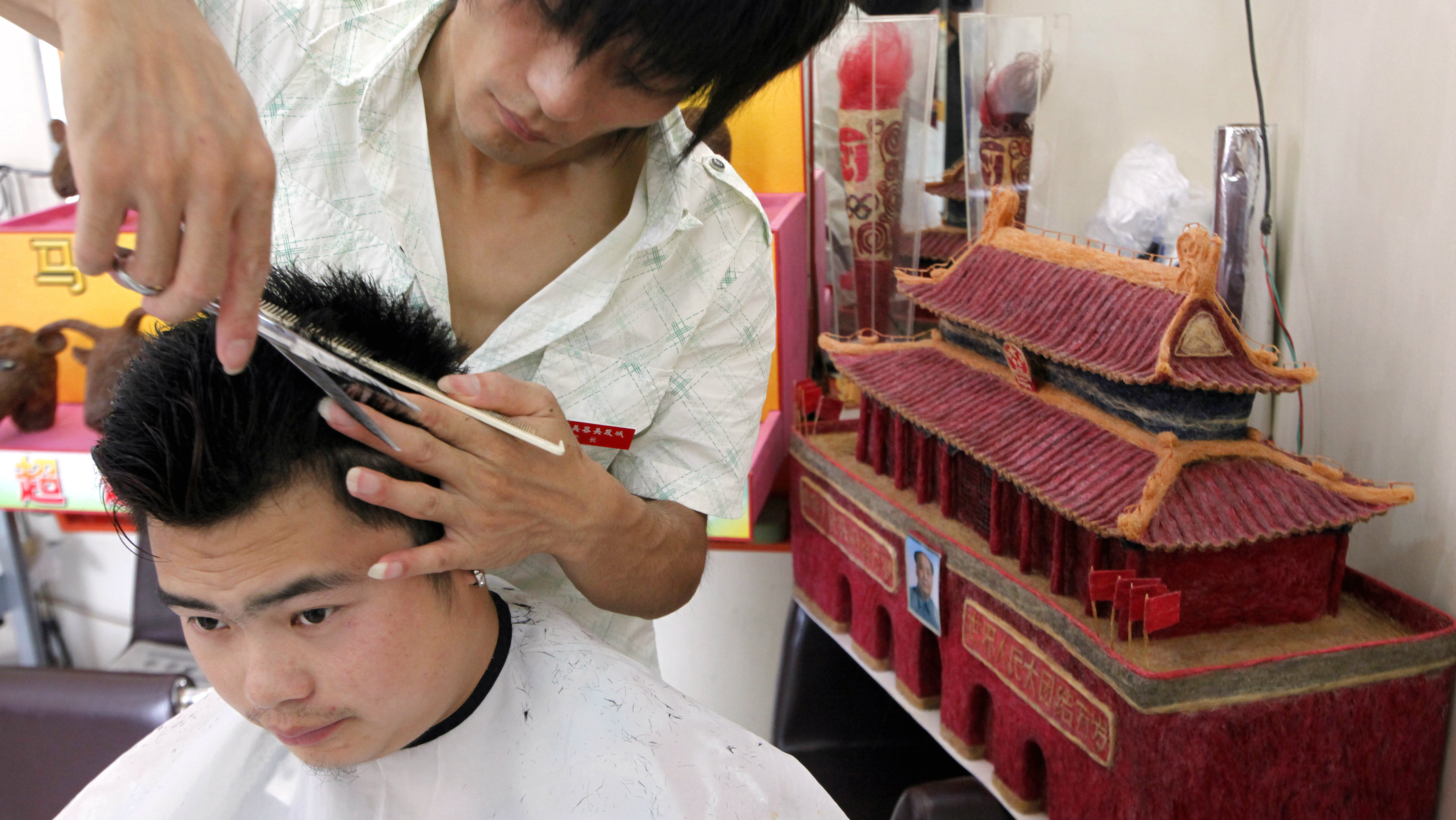 Chinese hairdresser Huang Xin (R) cuts the hair of a customer in front of replicas of the Tiananmen Gate and Olympic torches that he made from human hair at his barbershop in Beijing August 3, 2009. Huang used 11kg (24 lbs) of hair cut from his customers over a five month period to create the Tiananmen Gate replica. Huang started making reproductions from human hair in early 2008, including the Beijing Olympic stadium (also known as the Bird's Nest), the National Aquatics Centre (also known as the Water Cube), and the Olympic rings.