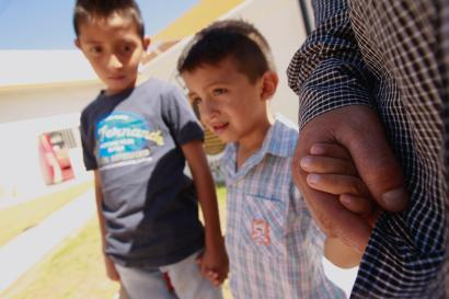 Salvadoran migrant Epigmenio Centeno and his sons, nine-year old Axel Jaret (L) and three-year old Steven Atonay, pose for a photograph outside the shelter House of the Migrant, after Epigmenio decided to stay with his children in Mexico due to U.S. President Donald Trump's child separation policy, in Ciudad Juarez, Mexico