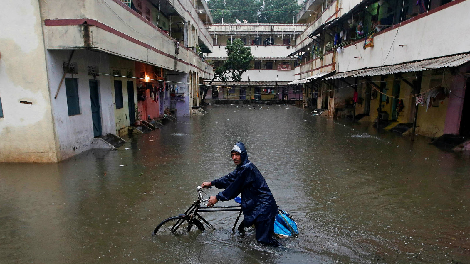 A delivery boy pushes his bicycle through a water-logged street after heavy rains at a residential colony in Mumbai, India September 20, 2017