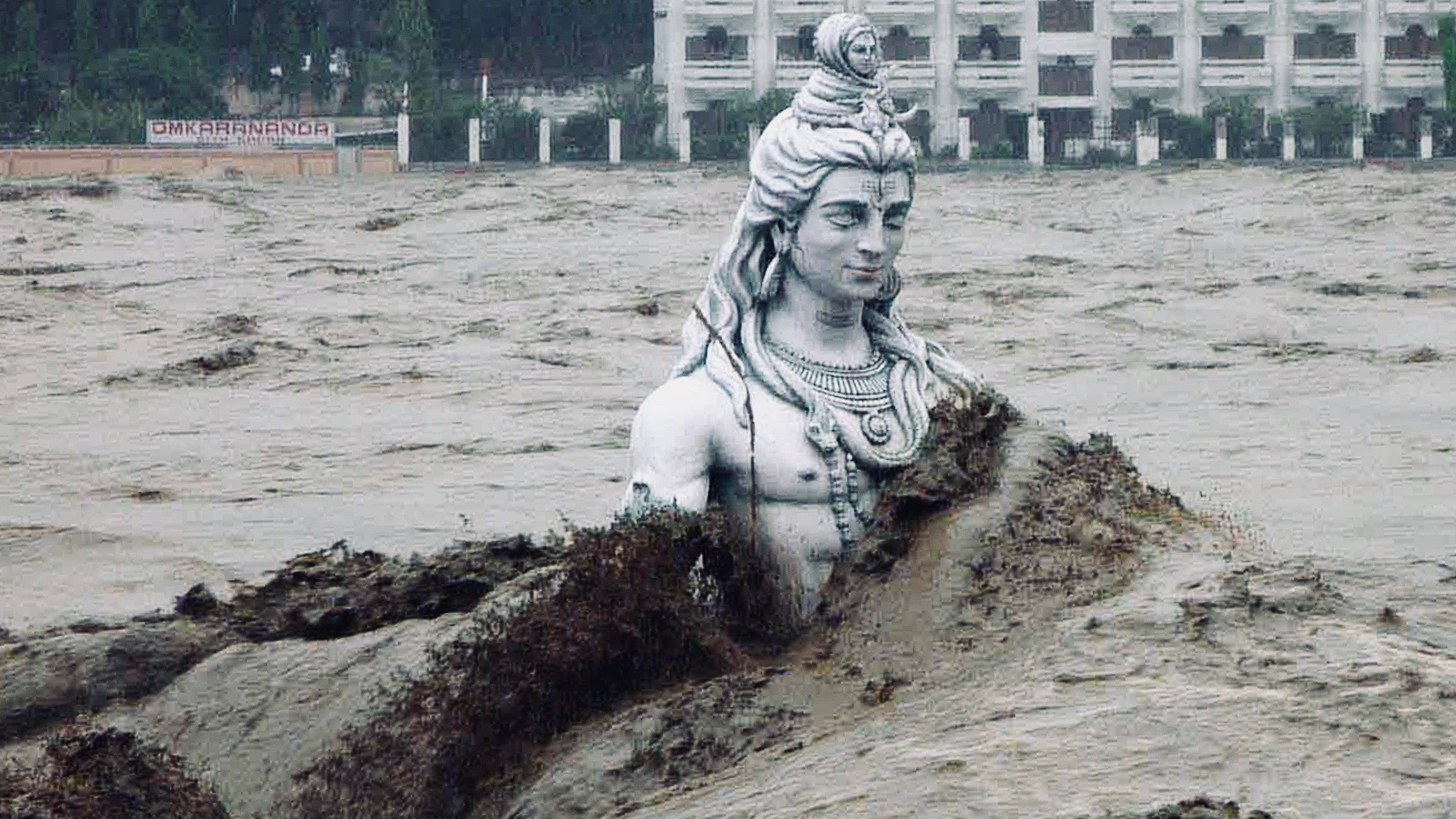 A submerged statue of the Hindu Lord Shiva stands amid the flooded waters of river Ganges.