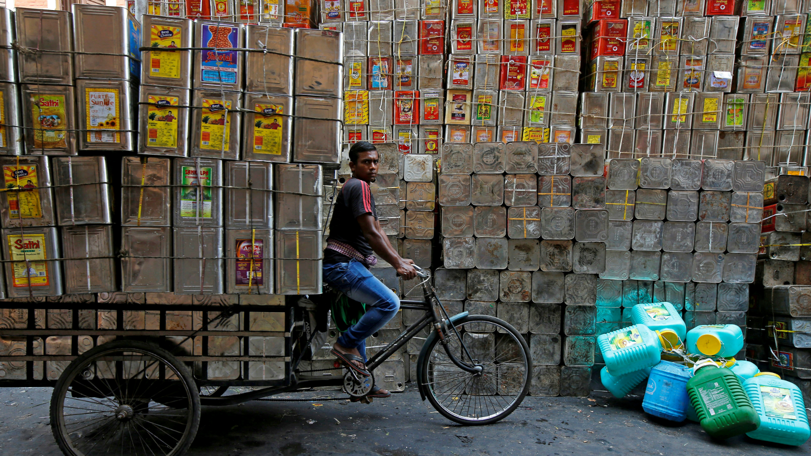 A man pedals a tricycle loaded with empty cooking oil containers in Kolkata, India, April 17, 2018.