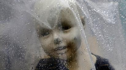 A mannequin is covered with a plastic sheet to prevent from rains outside a garments store in Mumbai, India, Saturday, June 23, 2018. India's western state of Maharashtra enforced its state-wide ban on a wide range of single-use plastic items including disposable cutlery and thermocol. (AP Photo/Rajanish Kakade)