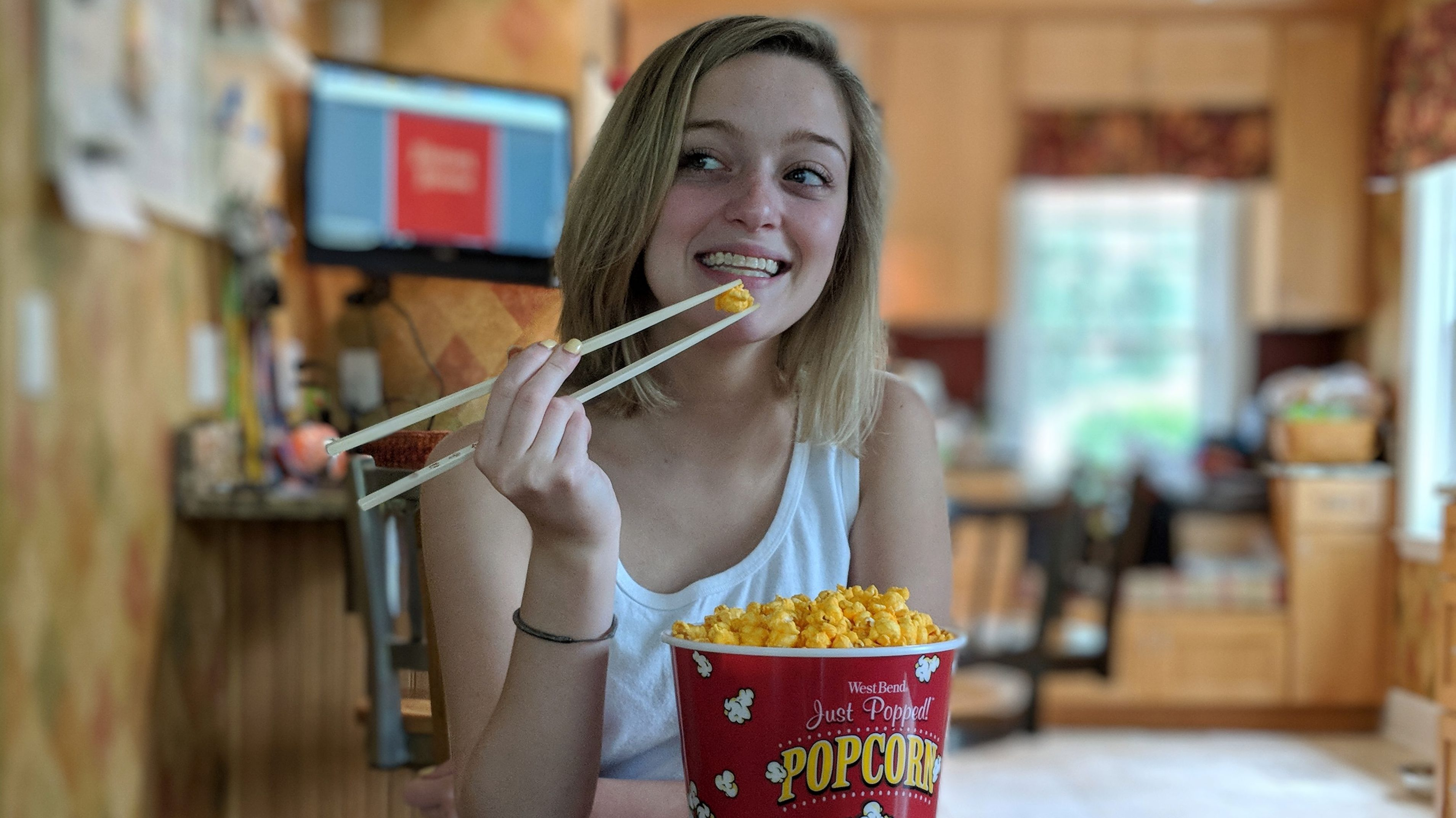 A woman eating popcorn with chopsticks