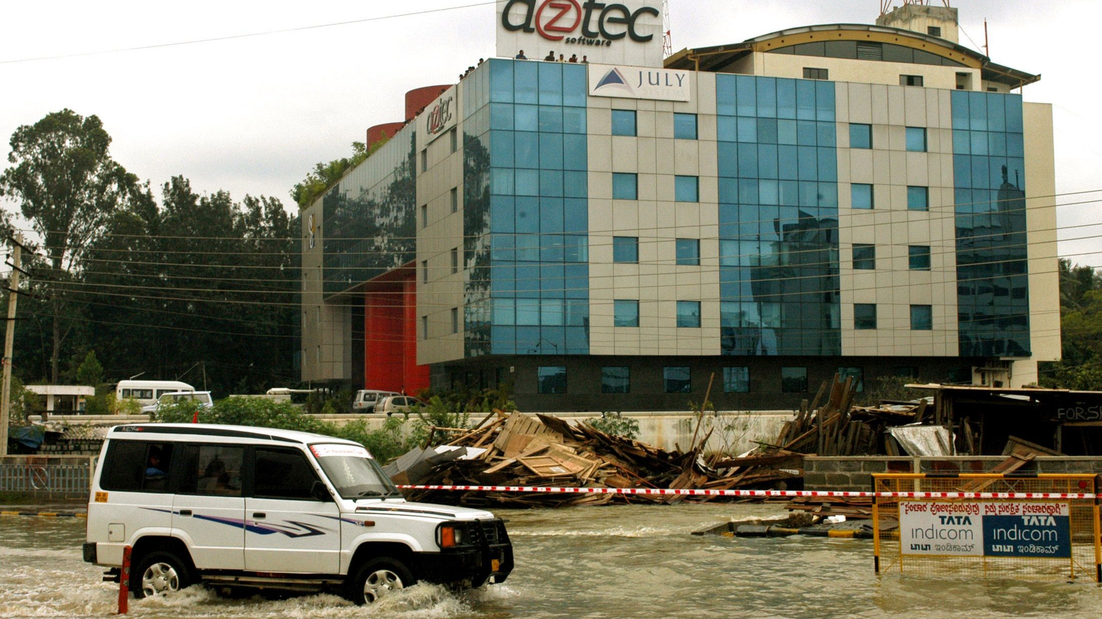 A vehicle moves on a flooded road in the southern Indian city of Bangalore, October 26, 2005. Police in India's technology capital, Bangalore, have urged motorists to stay off the city's roads as storms caused flooding and uprooted trees, but business was largely unaffected, officials said on Wednesday. REUTERS/Jagadeesh Nv - RP2DSFIFWNAB