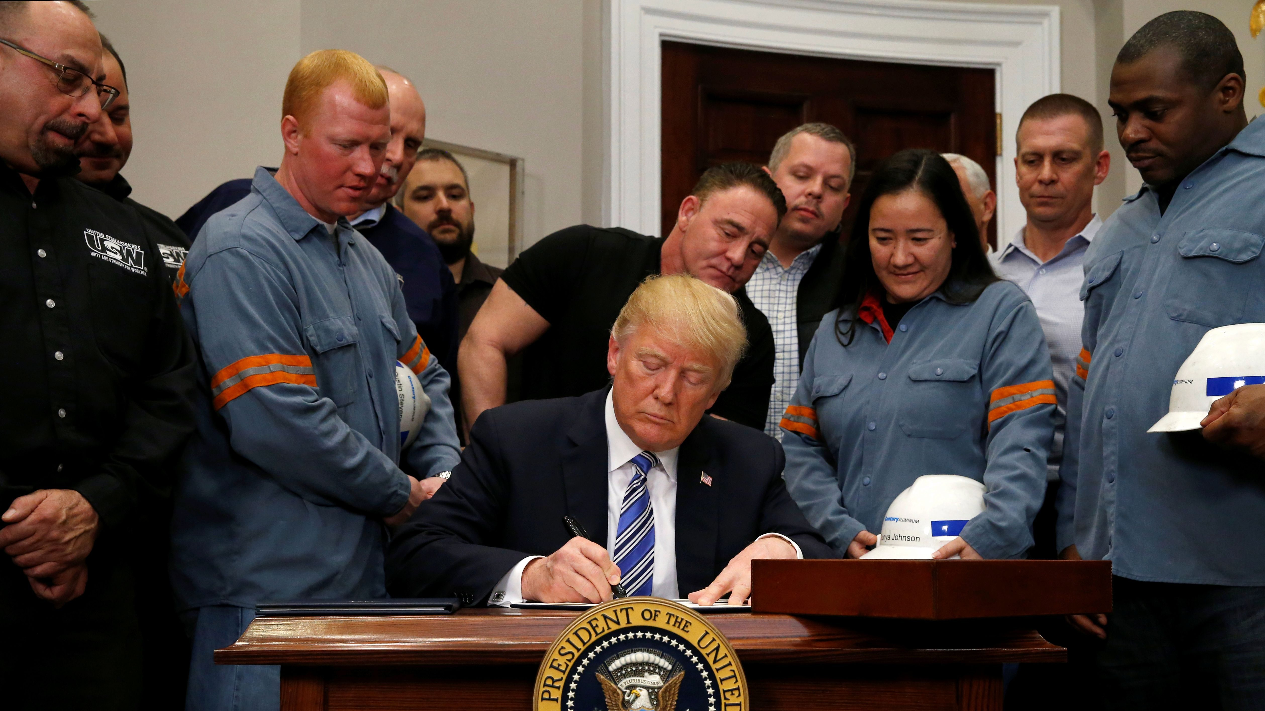U.S. President Donald Trump signs a presidential proclamation placing tariffs on steel and aluminum imports while surrounded by workers