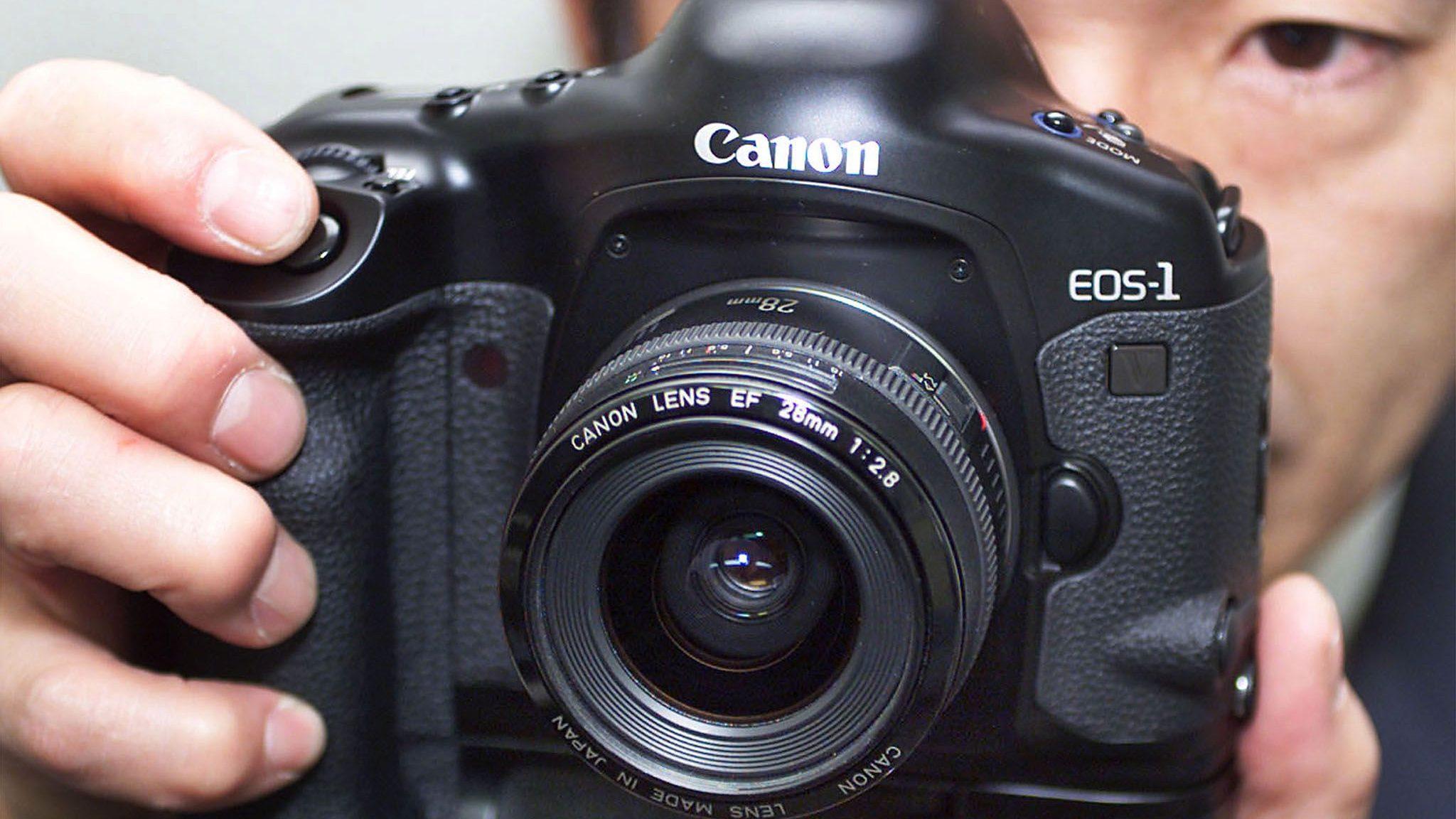 Canon employee Yoshinobu Ohkawaguchi holds the new EOS-1V camera in Tokyo February 2. Canon Inc intr..