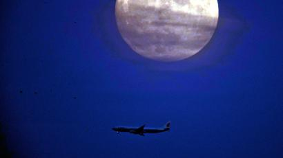 In this Tuesday, Dec. 13 2016, photo, a jet liner flies near the supermoon seen from Beijing, China. The supermoon phenomenon which occurs when the moon reaches a point closer than usual, shone brightly Tuesday night in Beijing, as the smog that often blankets China's capital city and most of the industrial north in winter subsided for the evening.