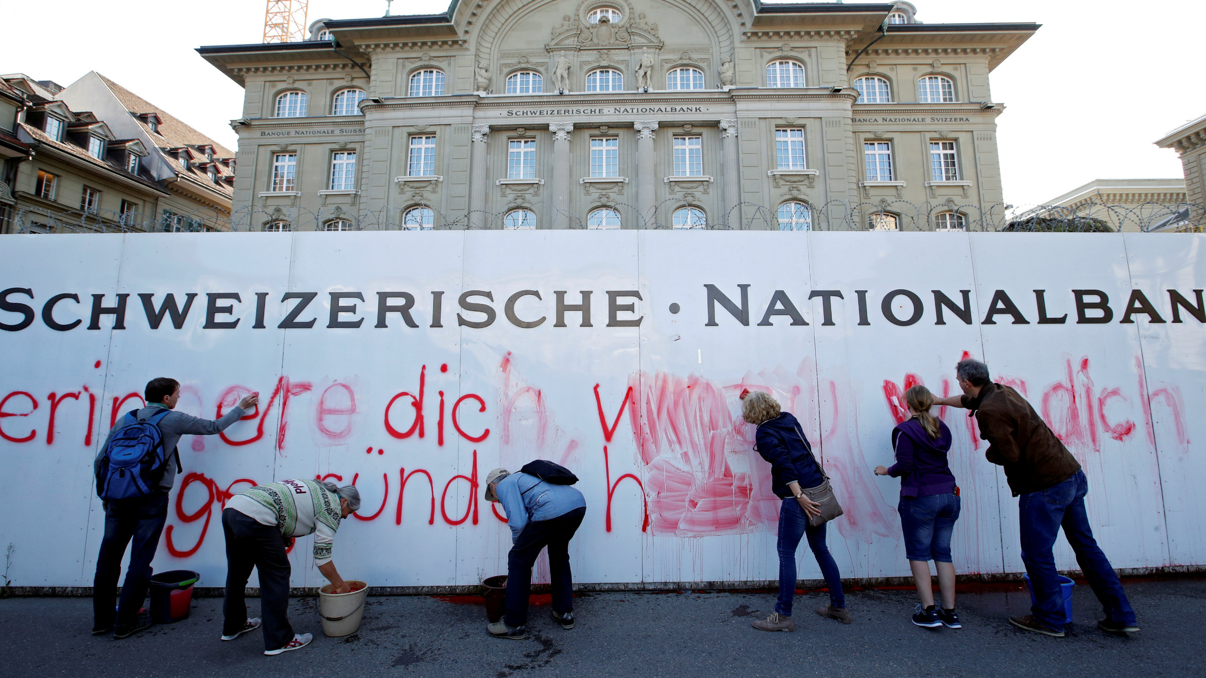 """Supporters of the """"sovereign money"""" initiative paint a slogan on a wall outside the Swiss National Bank"""