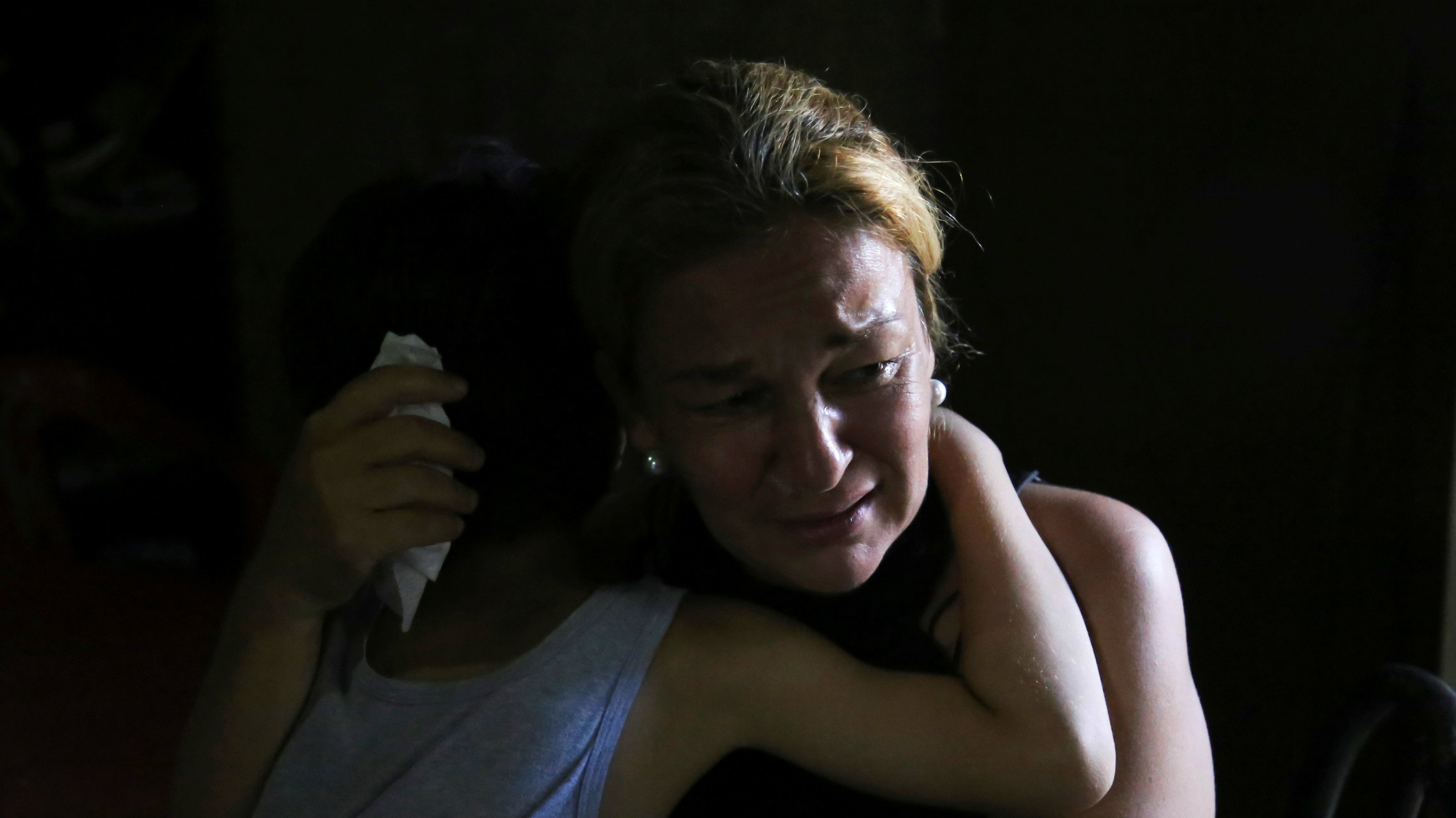 Yunni Perez cries while she hugs her son Luis during an interview with Reuters at their house in Caracas...