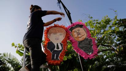 A staff member of a local Mexican restaurant displays pinatas with the caricatures of U.S. President Donald Trump and North Korean leader Kim Jong Un, ahead of the their upcoming summit, Thursday, June 7, 2018, in Singapore. U.S. President Donald Trump and North Korean leader Kim Jong Un will meet at the Capella Hotel, a luxury resort for nuclear talks next week in Singapore, the White House said Tuesday.