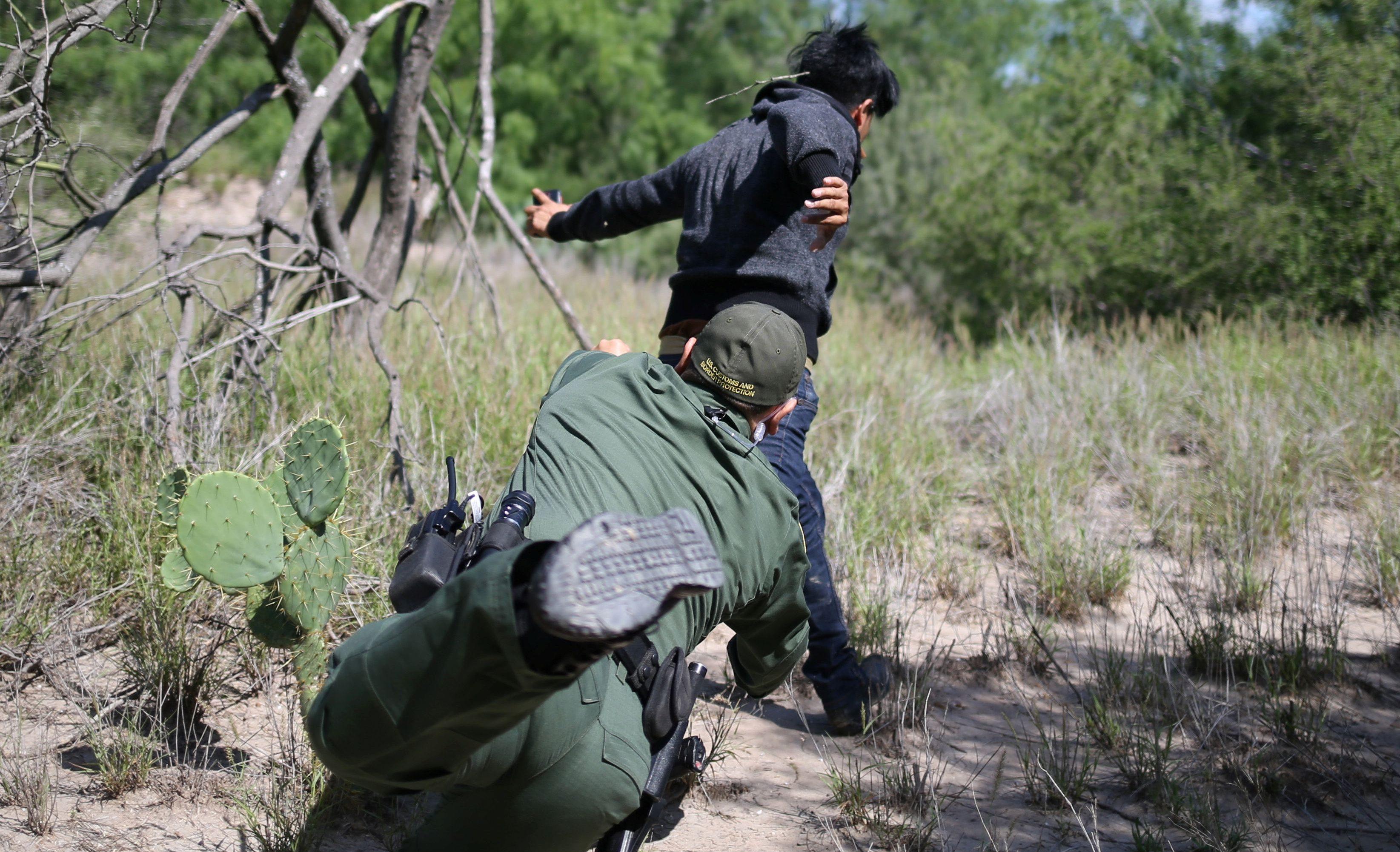 A man who illegally crossed the Mexico-U.S. border evades a U.S. Border Patrol agent near McAllen, Texas, U.S., May 8, 2018.