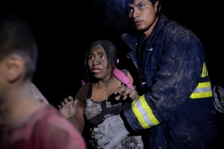 A rescue worker helps a woman covered with ash after Fuego volcano erupted violently in El Rodeo, Guatemala June 3, 2018. REUTERS/Fabricio Alonzo - RC1936B8FE70