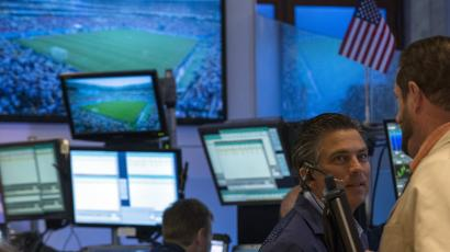 Screens show the 2014 World Cup soccer match between U.S. and Germany as traders work on the floor of the New York Stock Exchange