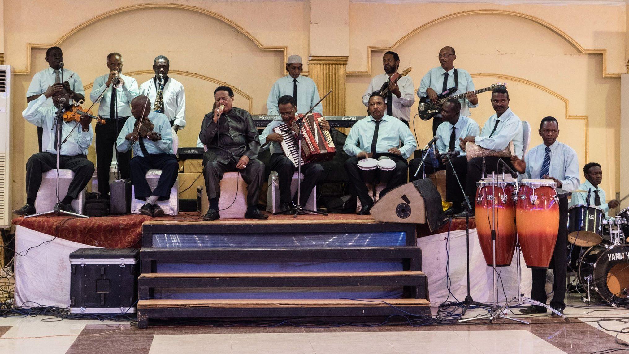 Legendary singer Salah Ben Al Badia (center in black) sings at a wedding in Omdurman, Sudan.