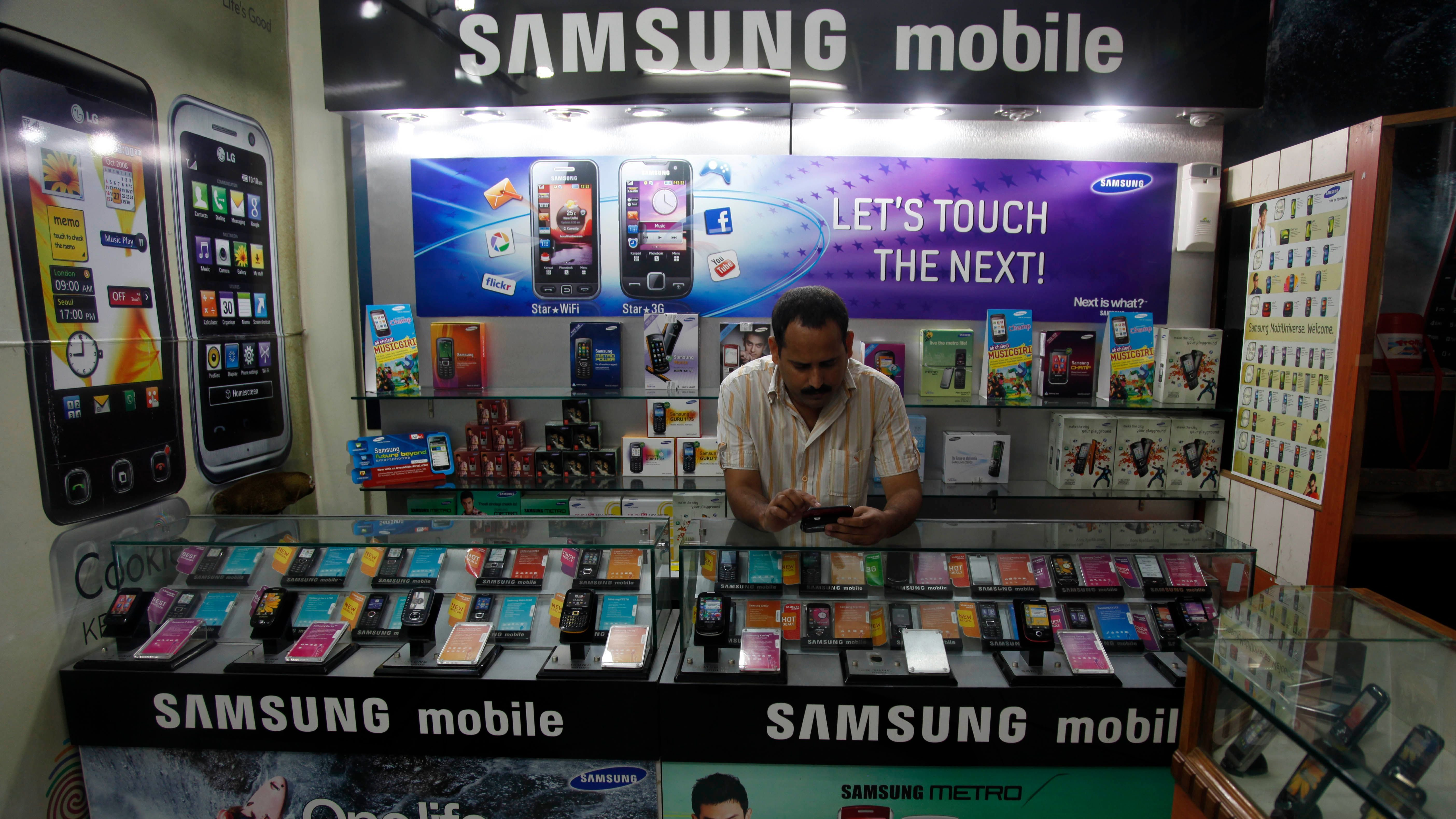 A shopkeeper stands in his shop displaying Samsung mobile advertisements in Allahabad, India, Thursday, Sept. 2, 2010. India has widened its security crackdown, asking all companies that provide encrypted communications, not just BlackBerry-maker Research In Motion, to install servers in the country to make it easier for the government to obtain users' data. Rajesh Chharia, president of the Internet Service Providers Association of India, said the government wants everyone, including RIM, Skype, Google, Nokia and MSN Hotmail, to give Indian security agencies more access to their user content. (AP Photo/Rajesh Kumar Singh)