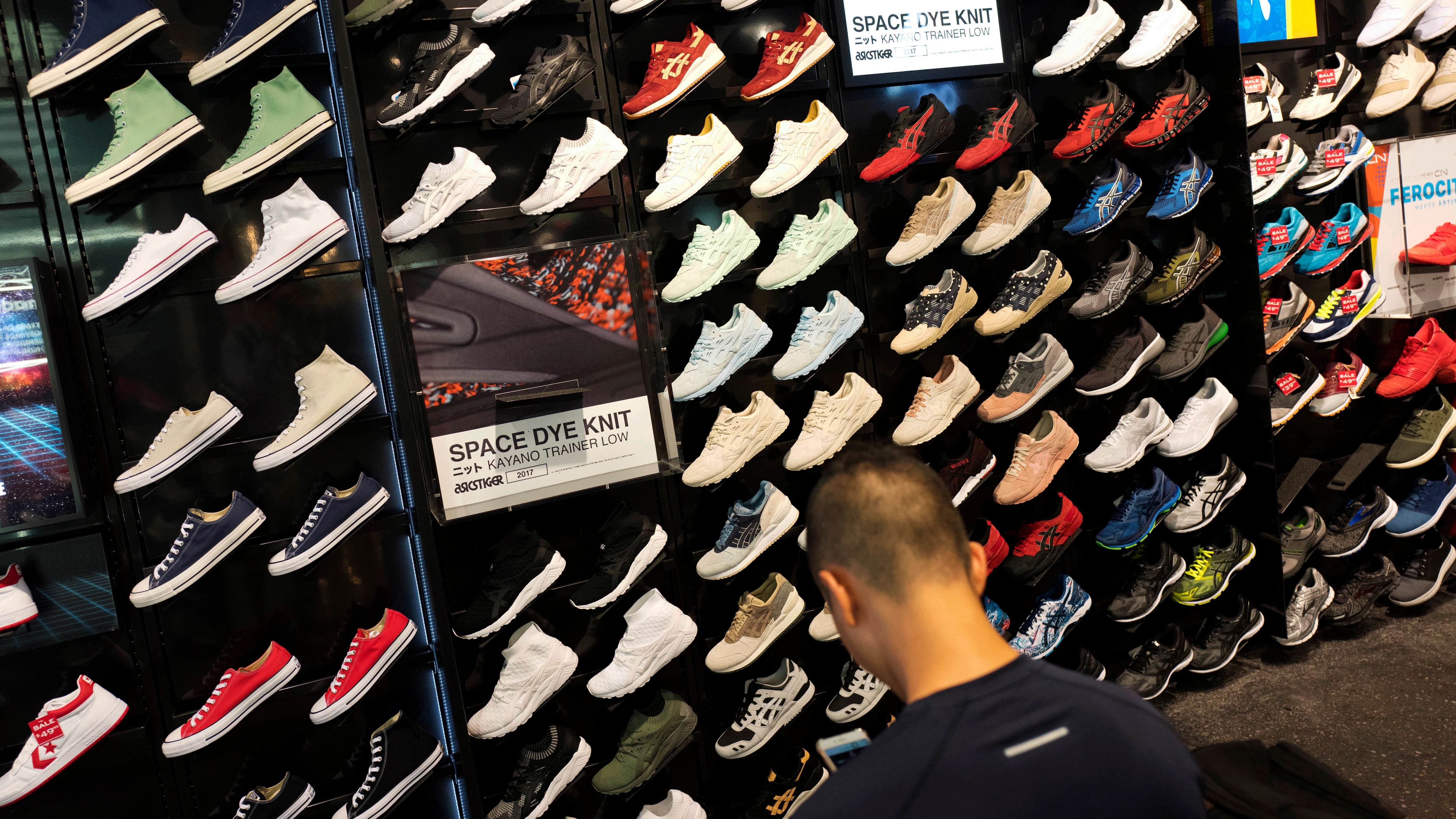 In this Tuesday, Aug. 22, 2017, photo, a customer looks at shoes at a Foot Locker in New York. On Friday, Sept. 15, 2017, the Commerce Department reports on business stockpiles in July. (AP Photo/Mark Lennihan)