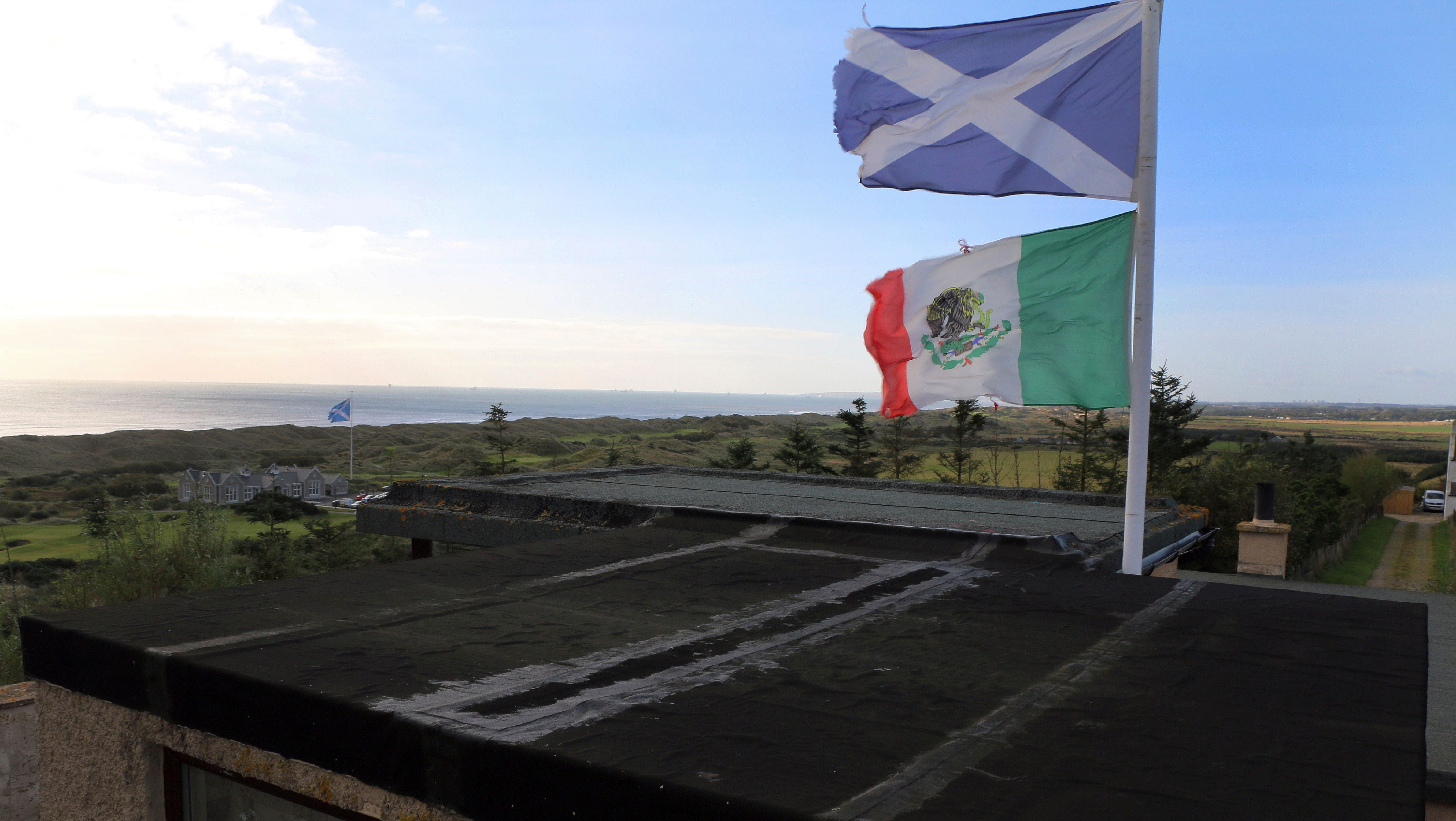 A Scottish flag, top, and the Mexican National flag fly from the home of David Milne overlooking the Trump International golf course., Friday Oct. 6, 2017. Feelings toward President Donald Trump run from anger to praise in Scotland where the troubles for the president's two golf clubs have only mounted recently. A financial report filed with the British government shows Trump is losing millions for a third year in a row. Shortly before Trump visited his North Sea resort in June last year, Milne ran a Mexican flag up a pole in protest against his immigration policies. (AP Photo/Renee Graham)