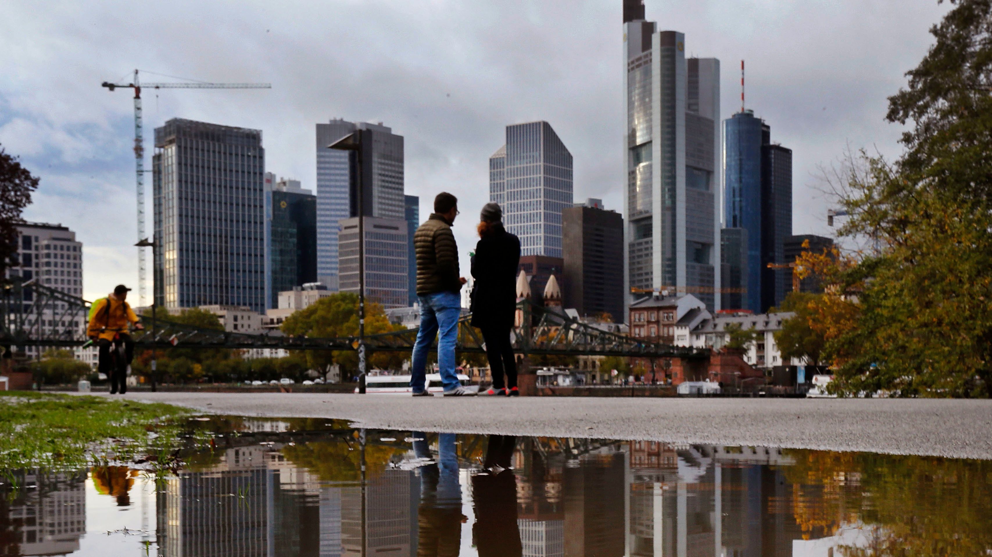 A leaf lies in a puddle where the skyline of the banking district is reflected in Frankfurt, Germany, on a rainy Sunday, Oct. 22, 2017. (AP Photo/Michael Probst)