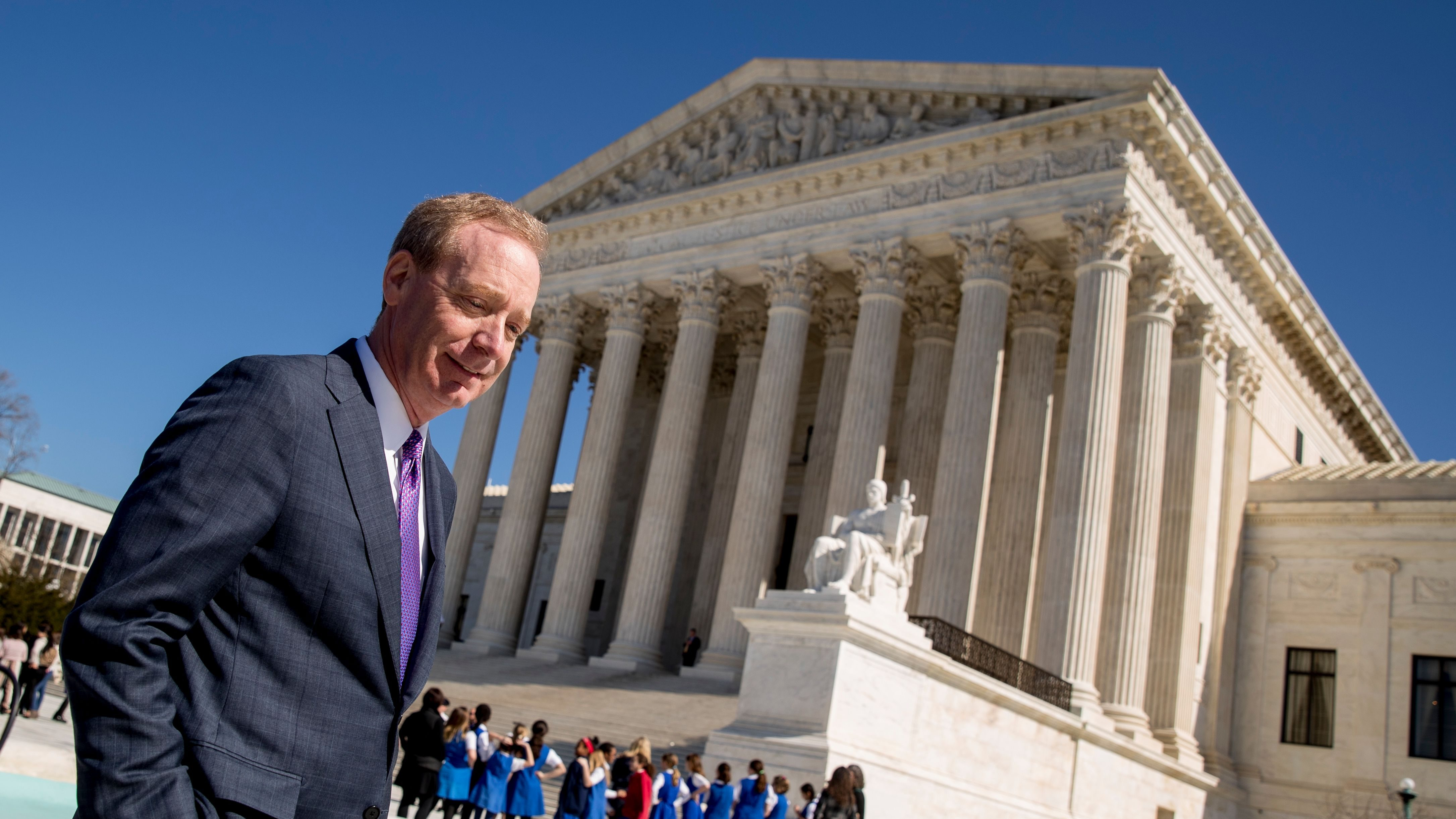 Microsoft President and Chief Legal Officer Brad Smith, left, leaves the Supreme Court, Tuesday, Feb. 27, 2018, in Washington. The Supreme Court heard arguments Tuesday in a dispute between the Trump administration and Microsoft Corp. over a warrant for emails that were sought as part of a drug trafficking investigation.(AP Photo/Andrew Harnik)