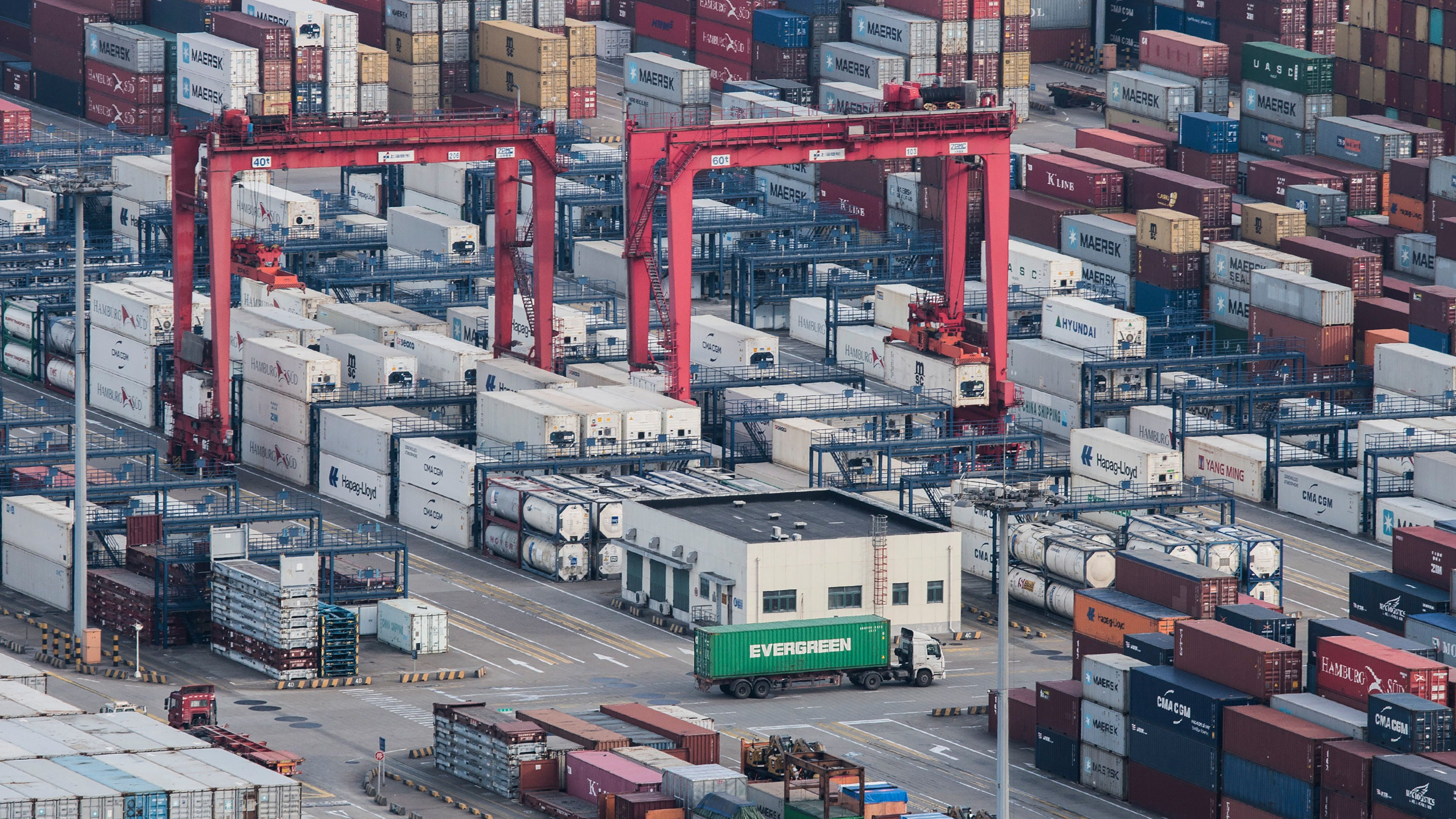 """A cargo truck drives amid stacked shipping containers at the Yangshan port in Shanghai, Thursday, March 29, 2018. China's Commerce Ministry called on Washington on Thursday to discard planned tariffs it warned might set off a chain reaction that could disrupt global trade and said Beijing will """"fight to the end"""". (AP Photo)"""