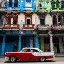 A red car driving in front of colorful buildings in Cuba.
