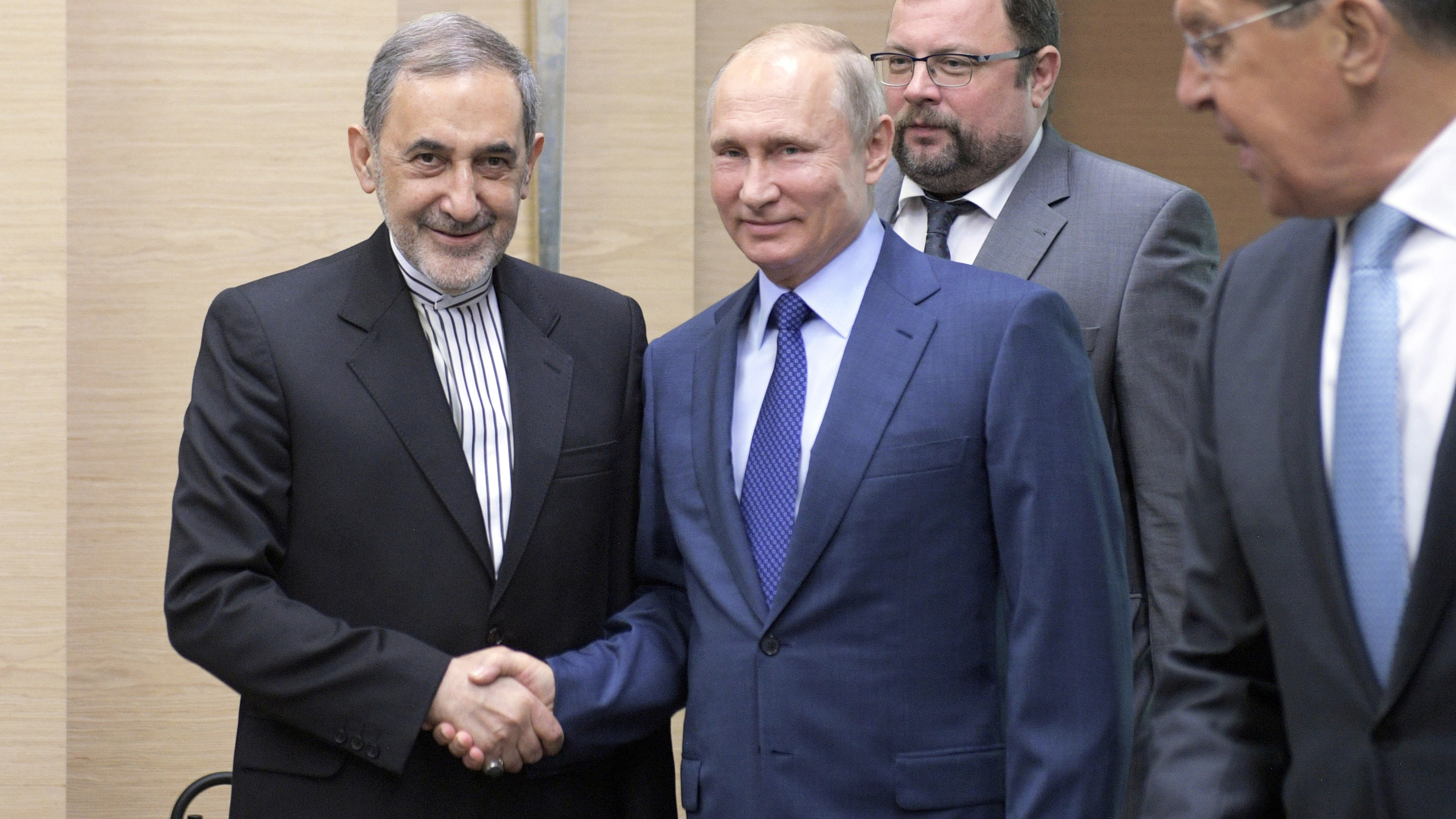 Russian President Vladimir Putin, center, shakes hands with Ali Akbar Velayati, a senior adviser to Iran's Supreme Leader Ayatollah Ali Khamenei, as Russian Foreign Minister Sergey Lavrov, stands at right, at Novo-Ograyovo outside in Moscow, Russia, Thursday, July 12, 2018. Putin has received the Iranian leader's top adviser hours after conferring with the Israeli prime minister about Iran's presence in Syria. (Alexei Druzhinin, Sputnik, Kremlin Pool Photo via AP)