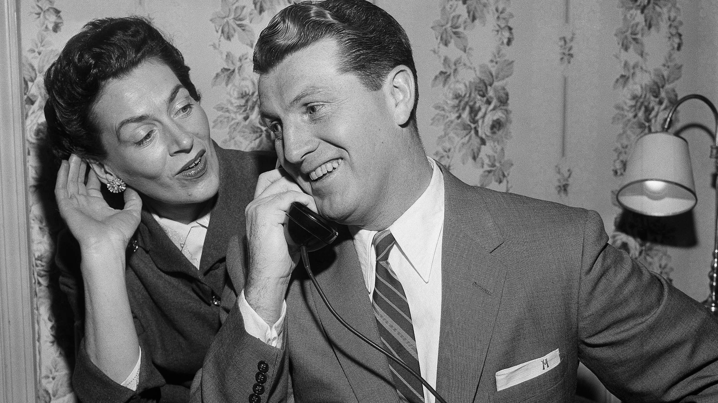 Basketball coach Frank McGuire speaks on the phone smiling while hie wife listens, in 1956