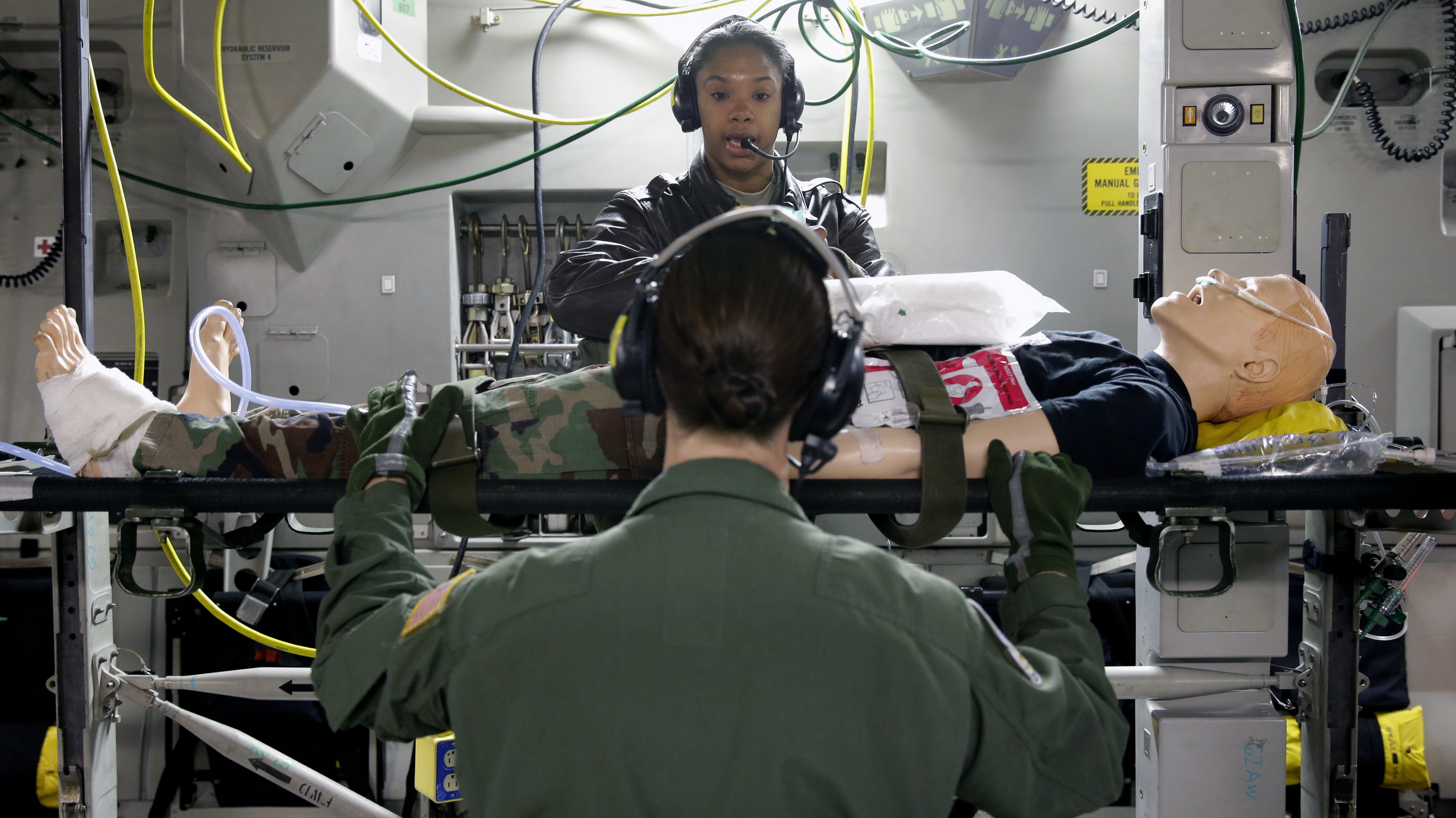 Master Sgt. Natalia Stockhausen, top, a flight medic with the Air Force Reserve 446th Aeromedical Evacuation Squadron, gives instructions as she works on a mannequin representing a medical patient during a training fight on a C-17 cargo plane out of Joint Base Lewis-McChord, Wash., Wednesday, Jan. 21, 2015. Most medical evacuations of wounded military members are performed by Air Force Reserve and Air National Guard units.