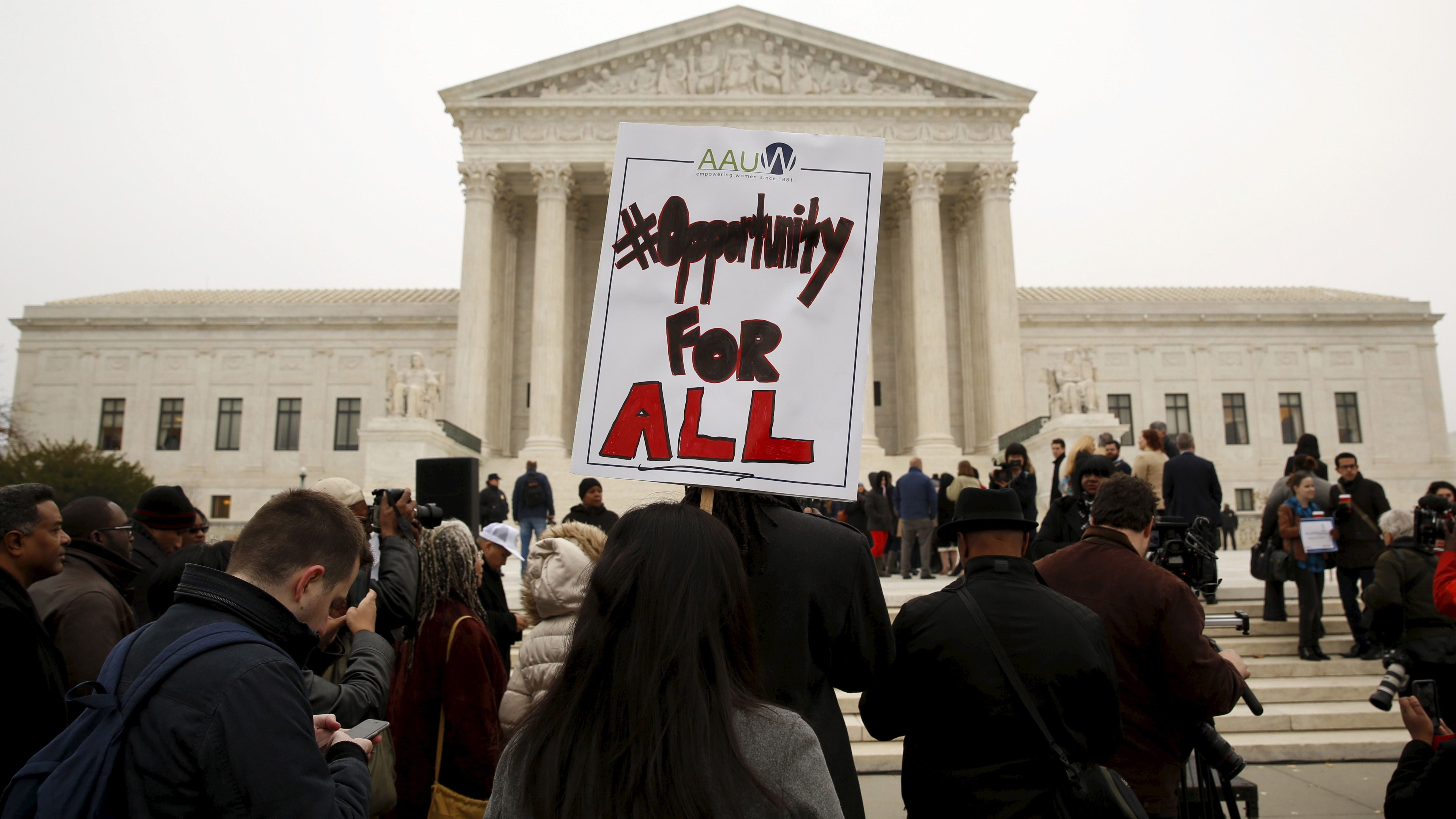 A demonstrator holds a sign aloft as the affirmative action in university admissions case was being heard at the Supreme Court in 2015.