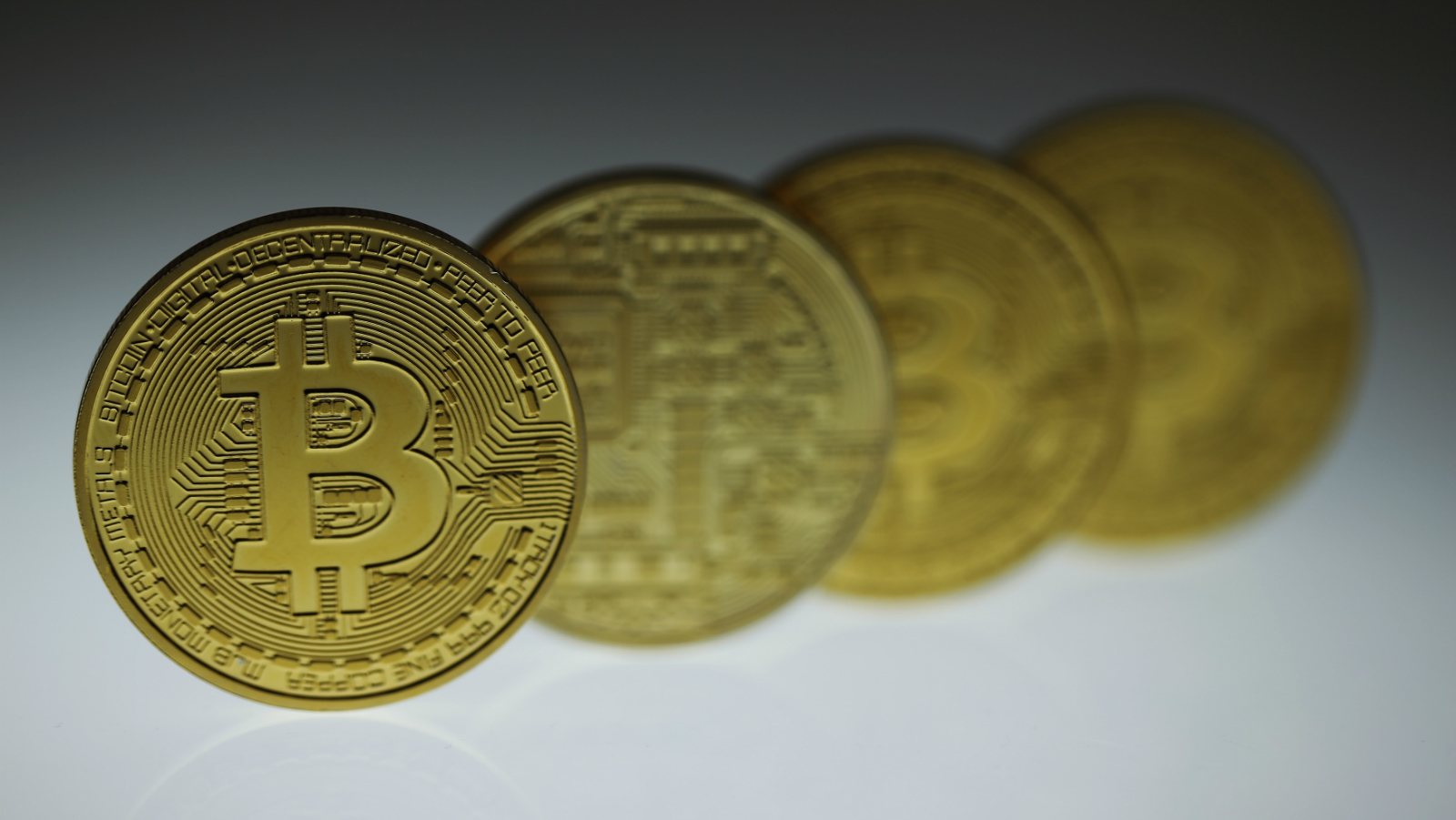 Mock Bitcoins are displayed on a table in an illustration picture taken in Berlin January 7, 2014. European banking regulators warn consumers against hacking and other risks associated with online currencies like Bitcoin. It follows similar advisories from the Bank of France and the Chinese central bank - and adds pressure to calls for the sector to be regulated.