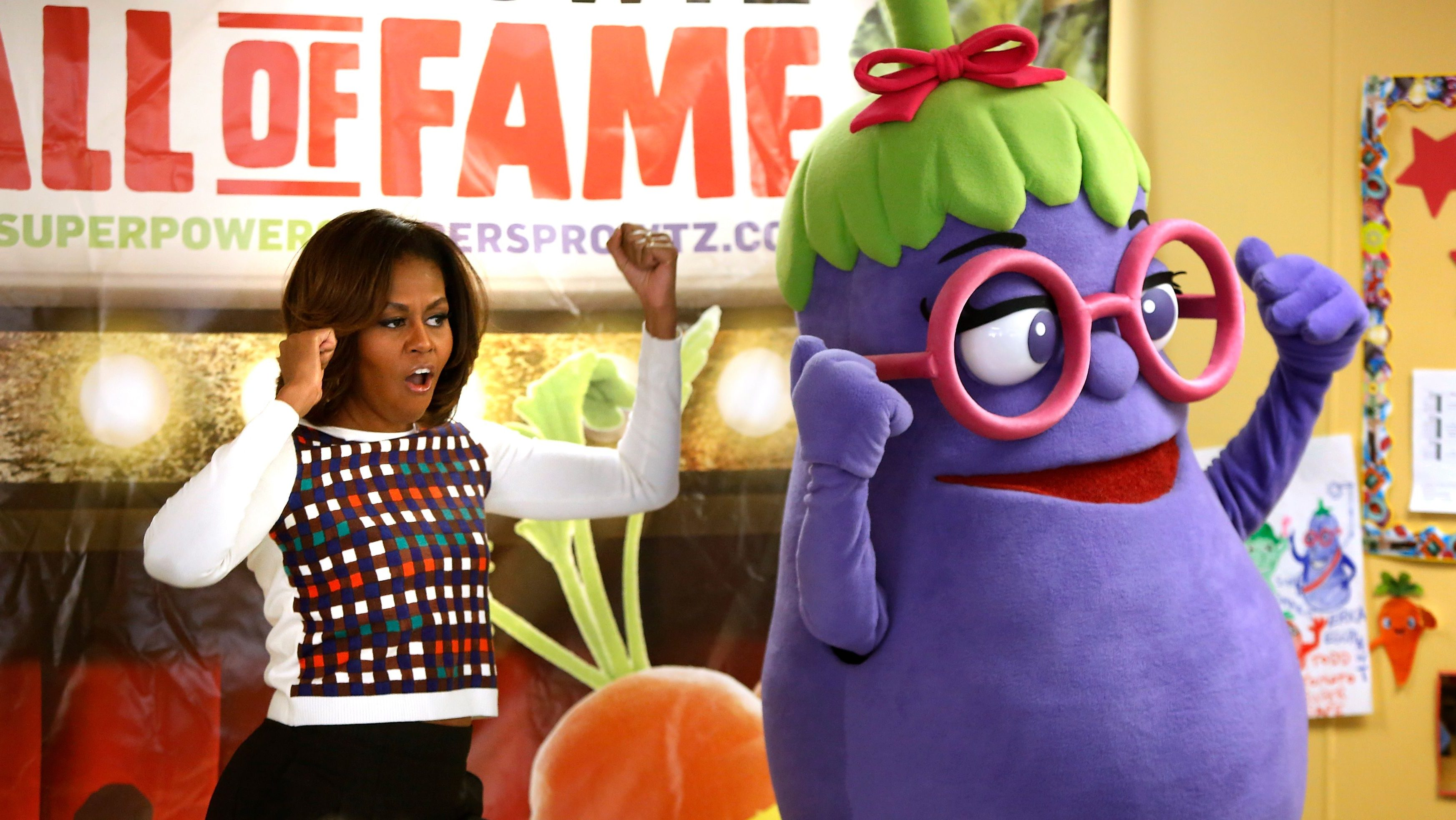 Former US first lady Michelle Obama dances with an eggplant from the Super Sprowtz at a La Petite Academy chid care center in Bowie, Maryland, on February 27, 2014.