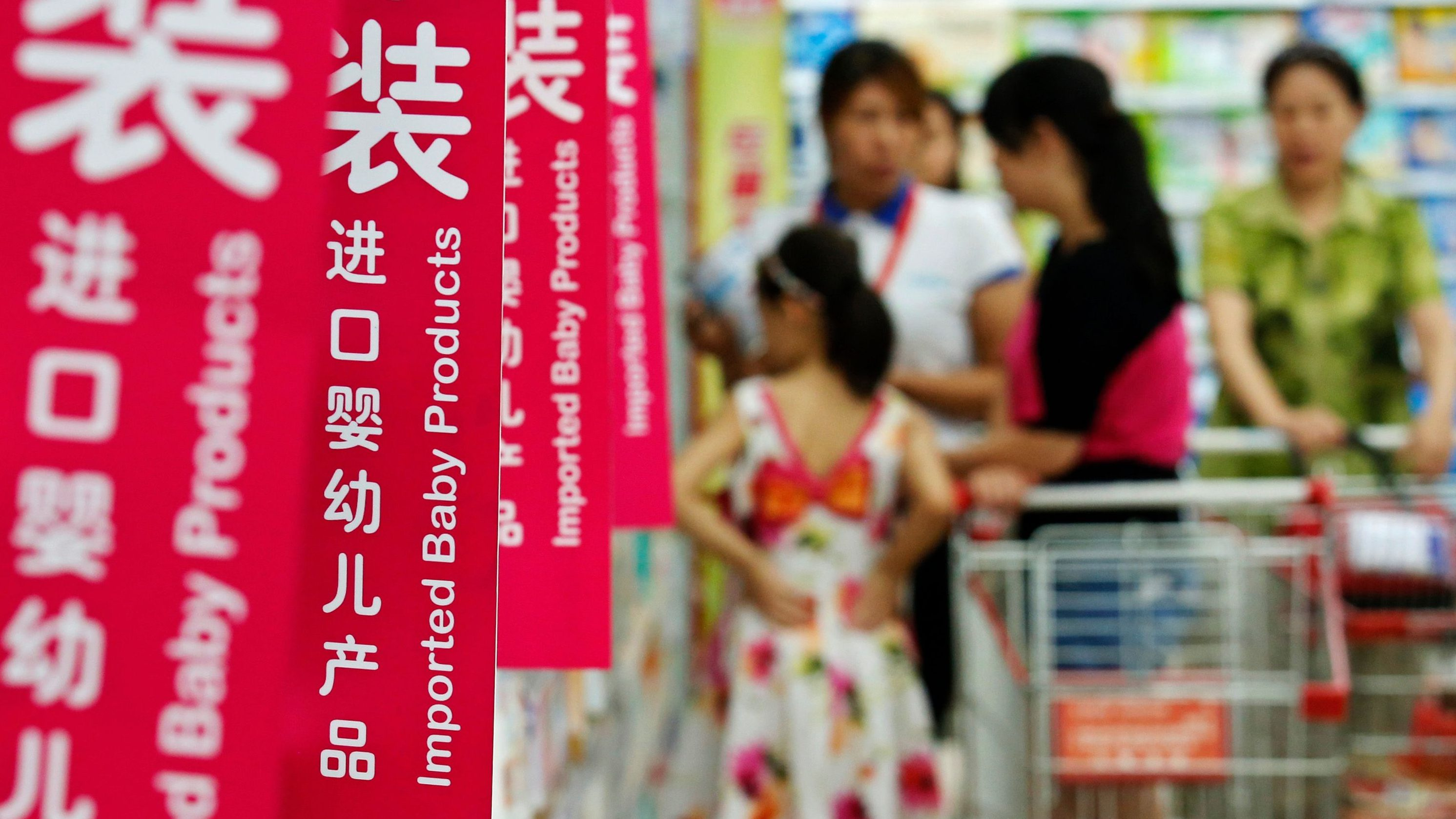 Customers talk to a sales assistant as they shop for milk powder in front of shelves displaying imported baby products at a supermarket in Beijing August 5, 2013. New Zealand's Fonterra apologised on Monday for a milk powder contamination scare in China that has raised safety concerns that threaten New Zealand's $9 billion annual dairy trade and Fonterra's own business in a top market.