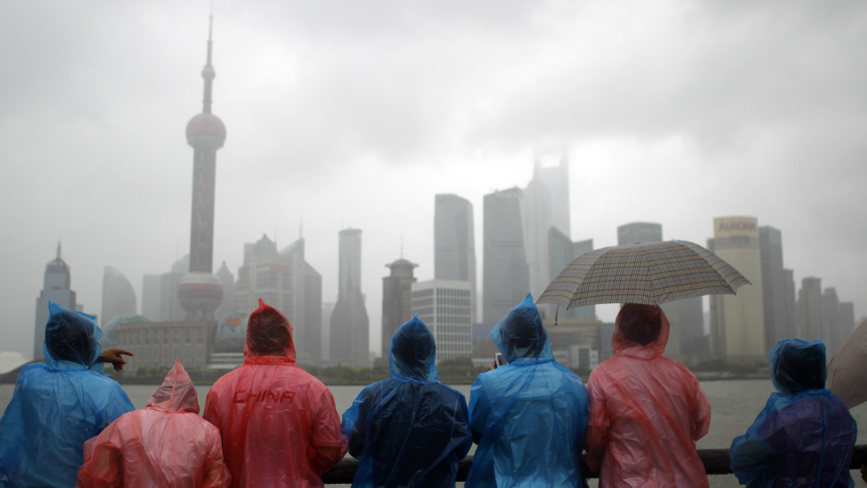 People looking at the Shanghai skyline during a rainstorm.