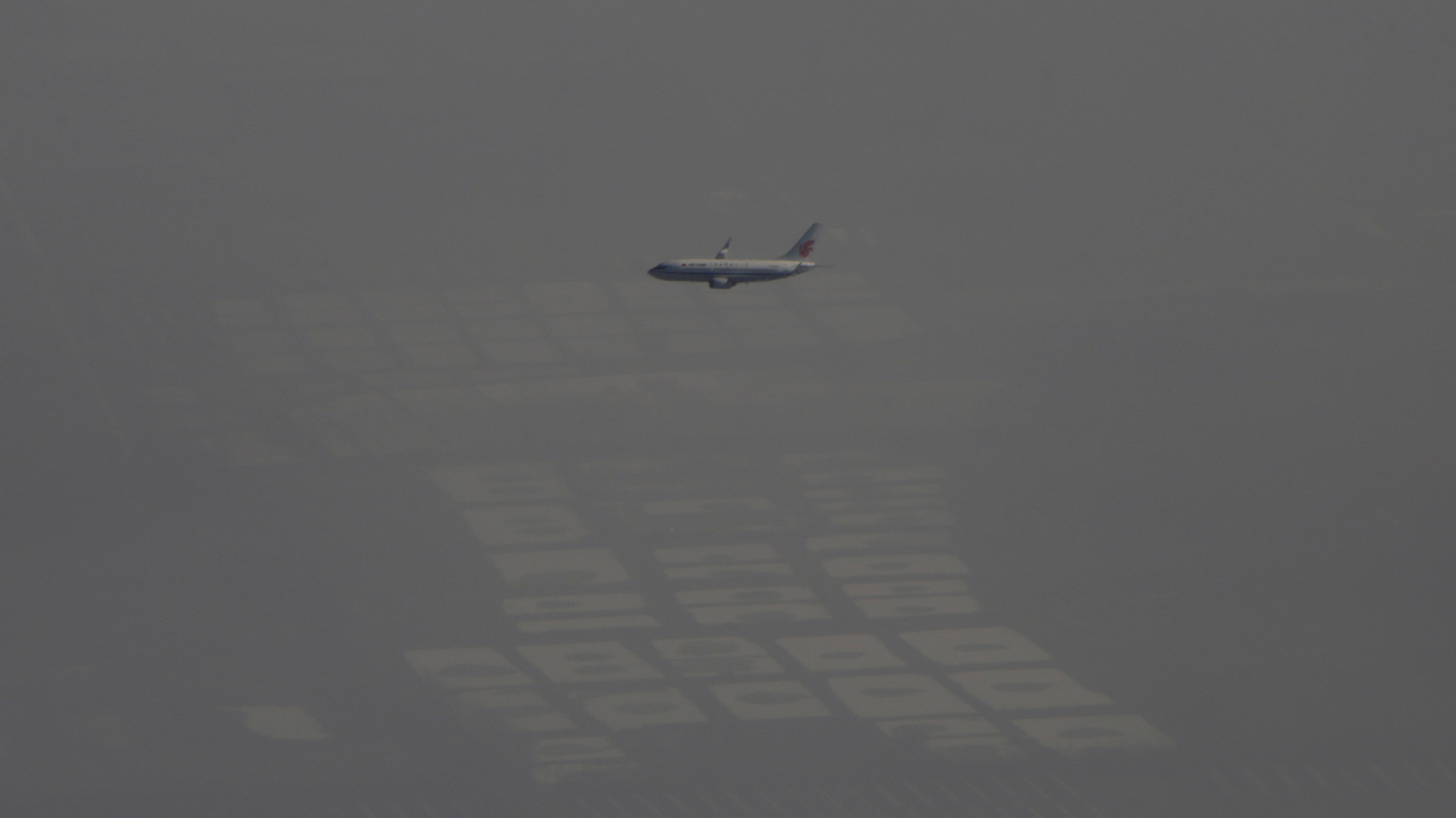 An Air China passenger aircraft flies amid heavy smog over the suburb of Beijing, China, January 2, 2017. REUTERS/Jason Lee - RC1852608AD0