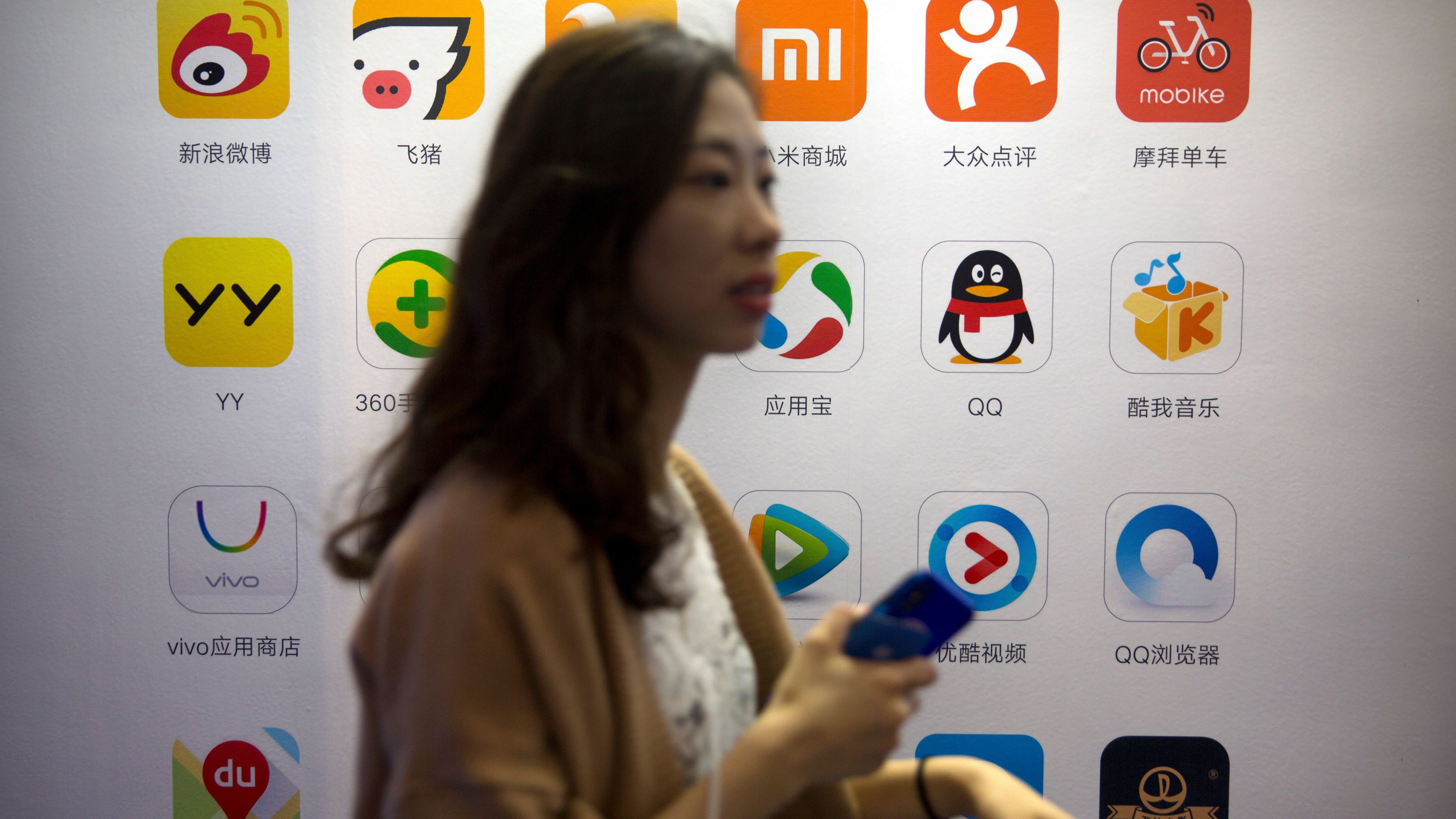 A woman holds her cellphone as she walks past a display showing the icons of popular Chinese smartphone apps at the Global Mobile Internet Conference (GMIC) in Beijing, Thursday, April 26, 2018. The GMIC features current and future trends in the mobile Internet industry by some major foreign and Chinese internet companies. (AP Photo/Mark Schiefelbein)
