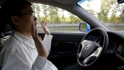 Li Zengwen, a development engineer at Changan Automobile, lifts his hands off the steering wheel as the car is on self-driving mode during a test drive on a highway in Beijing, China, April 16, 2016. REUTERS/Kim Kyung-Hoon - GF10000390806