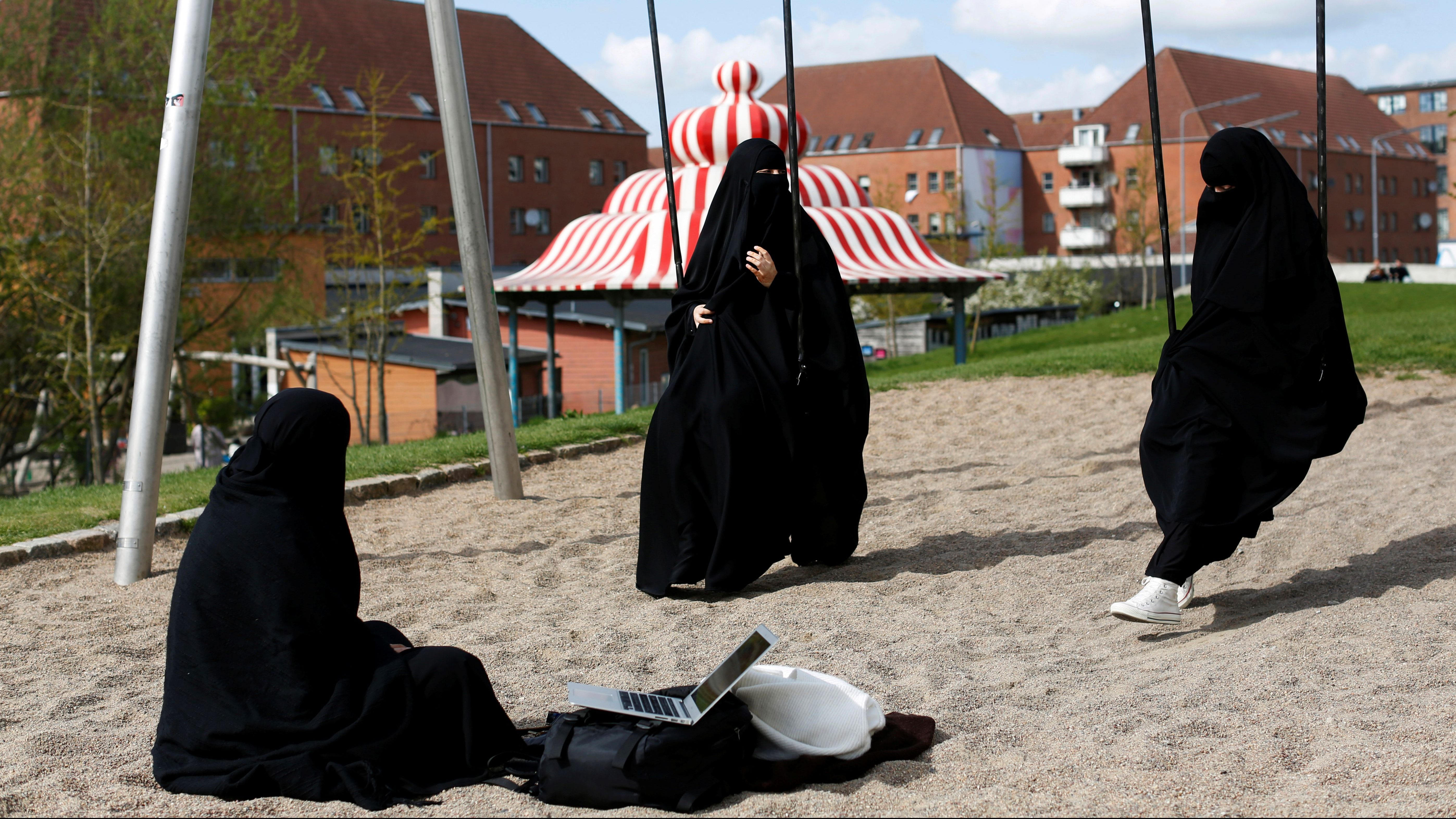 "Zaynab, who lives in Mjolnerparken, a housing estate that features on the Danish government's ""Ghetto List"", sits with her friends Amira and Sabrina in Superkilen, a recently designed urban renewal park that runs beside Mjolnerparken, in Copenhagen, Denmark, on May 3, 2018."