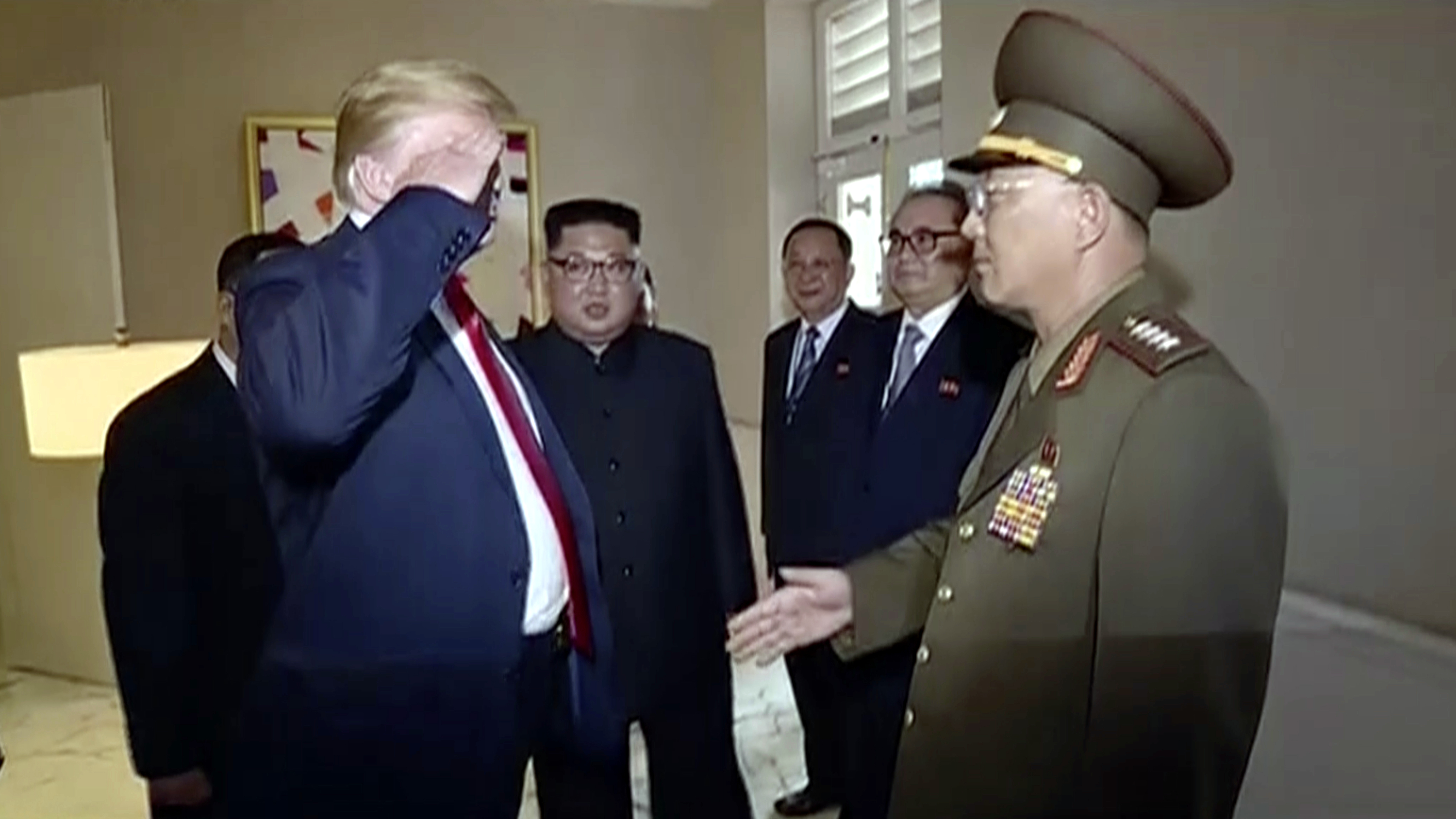 In this image made from June 12, 2018, video released by KRT, U.S. President Donald Trump salutes No Kwang Chol, minister of the People's Armed Forces of North Korea, as North Korean leader Kim Jong Un, center, introduces Trump to the general during the summit in Singapore.